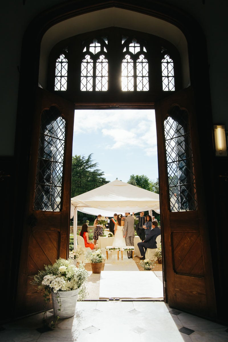 A shot of the bride and groom standing beneath a tent during ceremony, seen through a doorway at this destination wedding in Castello Dal Pozzo, Italy.
