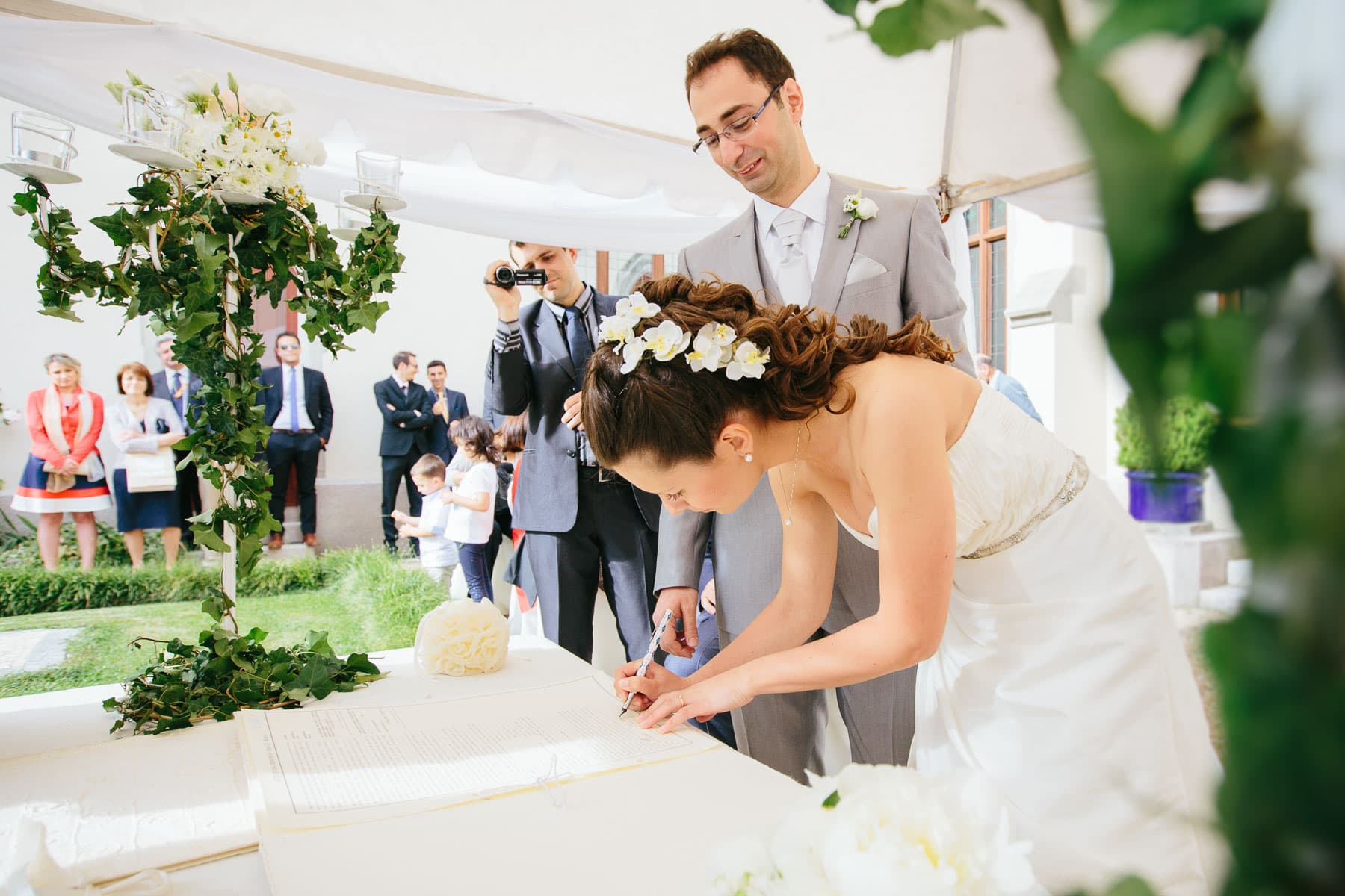 The bride signs the legal marriage documents as the groom watches in this destination wedding in Castello Dal Pozzo, Italy.