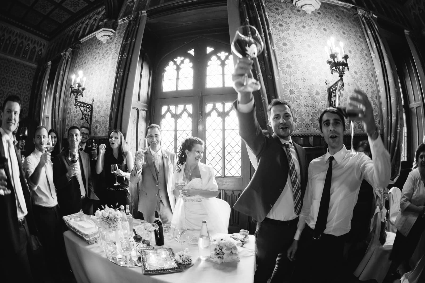 Guests raise a toast to the newly weds, towards the camera, in the reception hall at a destination wedding in Castello Dal Pozzo, Italy.