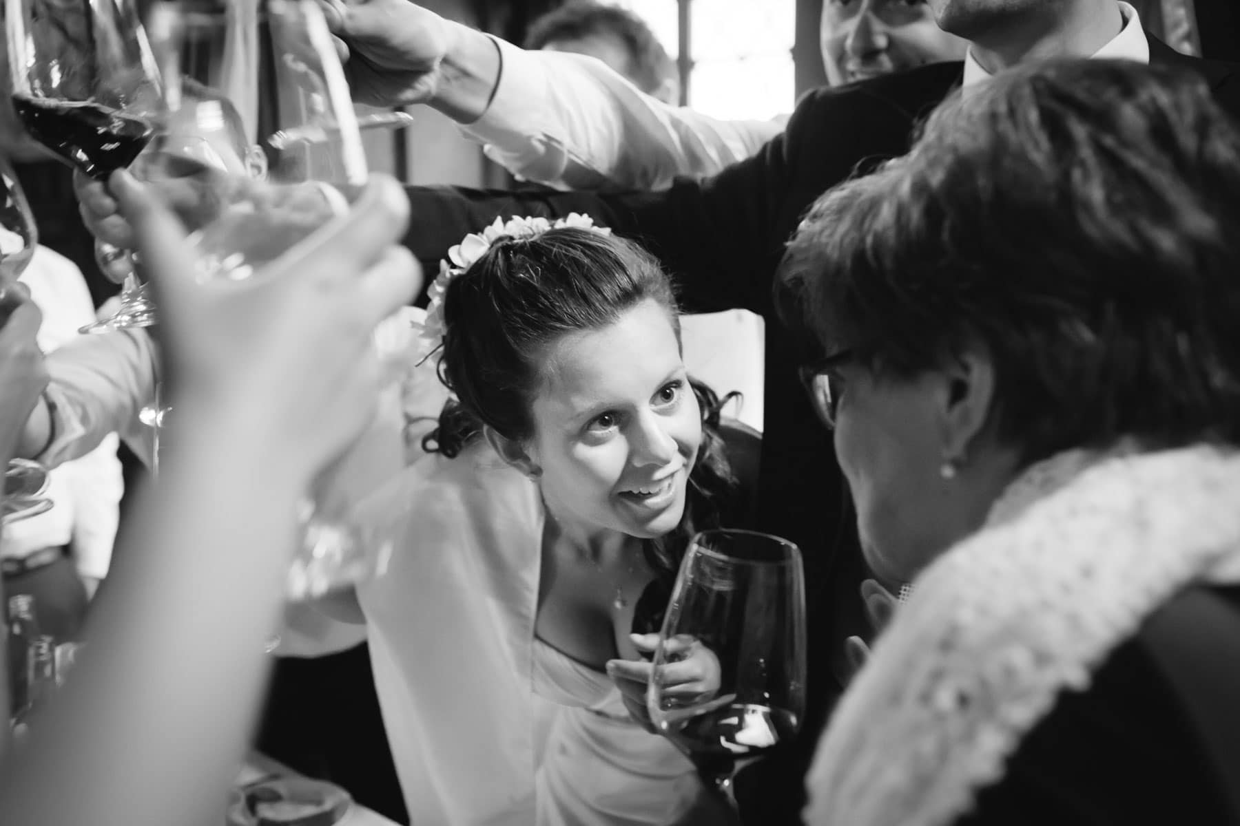 The bride exchanges some words with her mother as guests and groom raise a toast over her head during reception during a destination wedding in Castello Dal Pozzo, Italy.