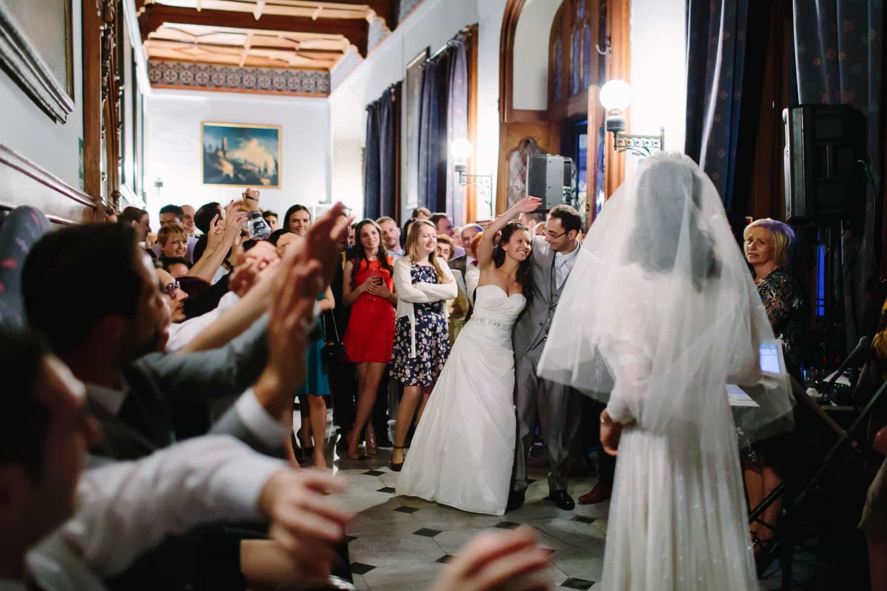Bride and groom sway along with their guests to their MCs signing in this grand hallway at a destination wedding in Castello Dal Pozzo, Italy.