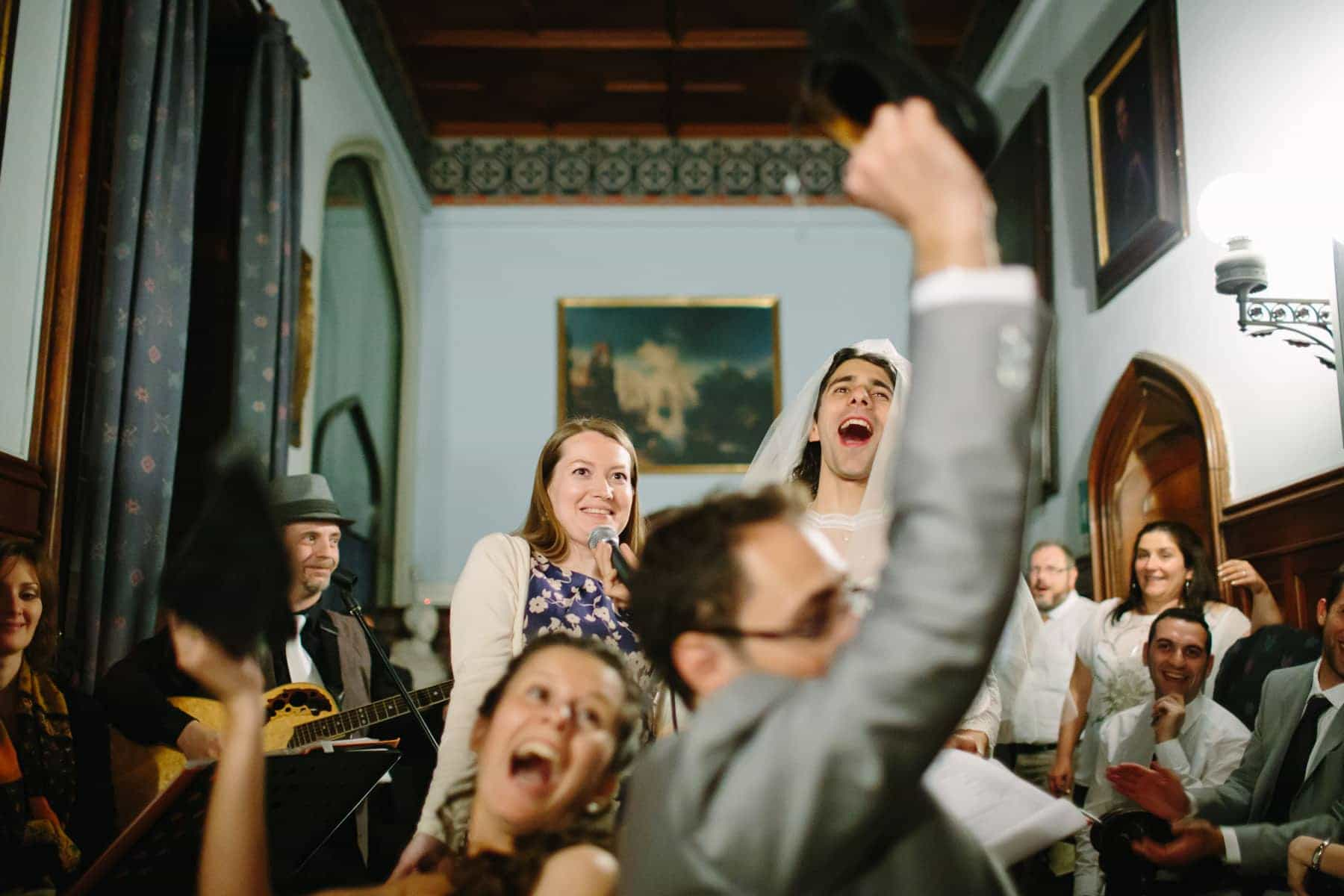 The MCs laugh as bride and groom play the shoe game in a grand hallway at this destination wedding in Castello Dal Pozzo, Italy.