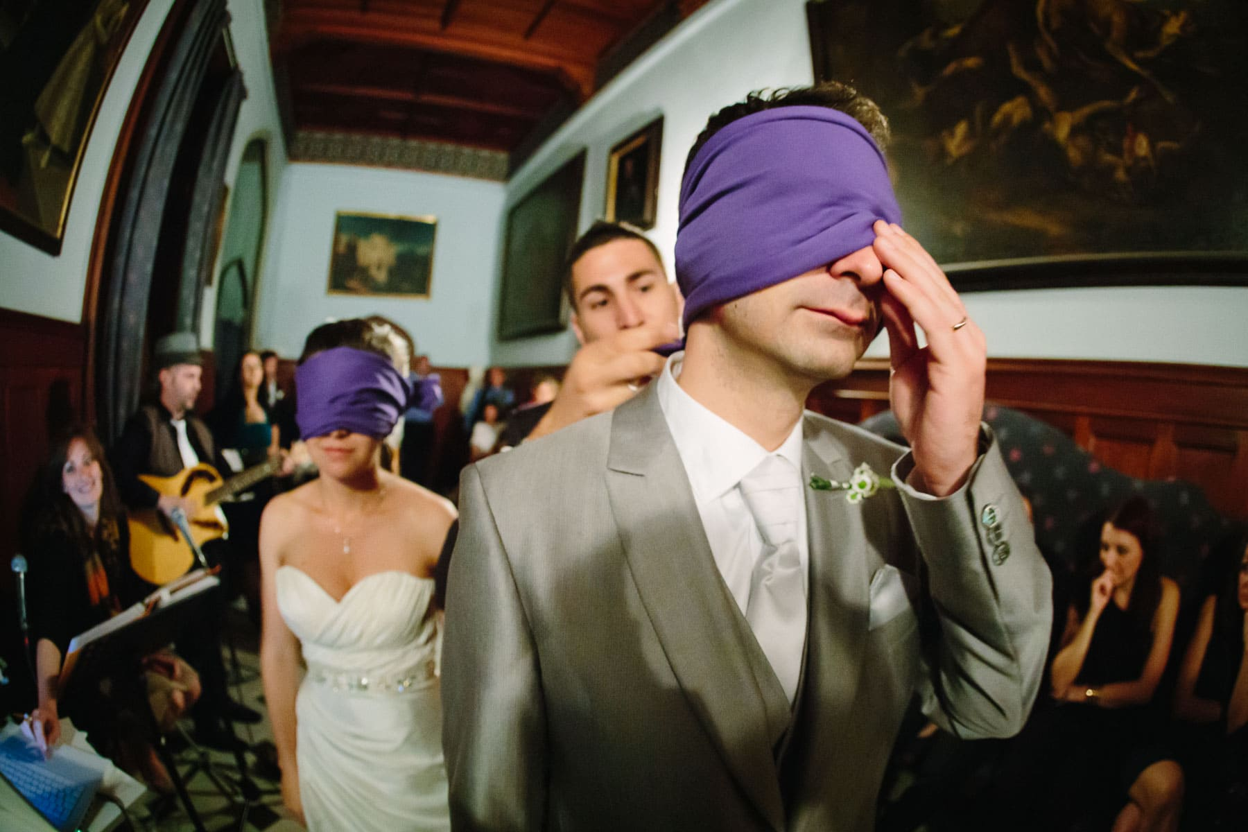 Bride and groom are blindfolded to entertain their guests in a grand hallway at a destination wedding in Castello Dal Pozzo, Italy.