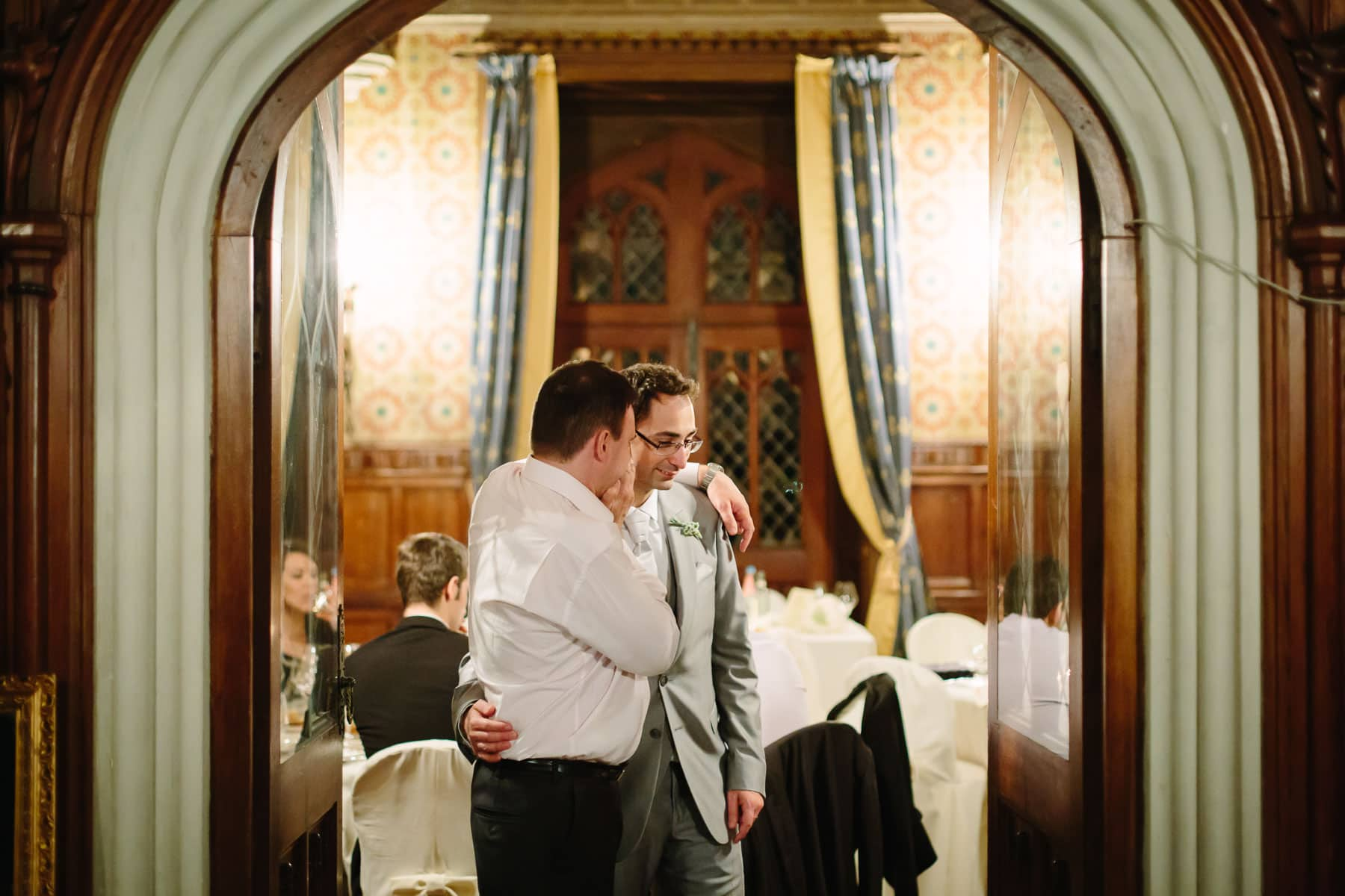 Groom and friend standing in large doorway in this destination wedding in Castello Dal Pozzo, Italy.