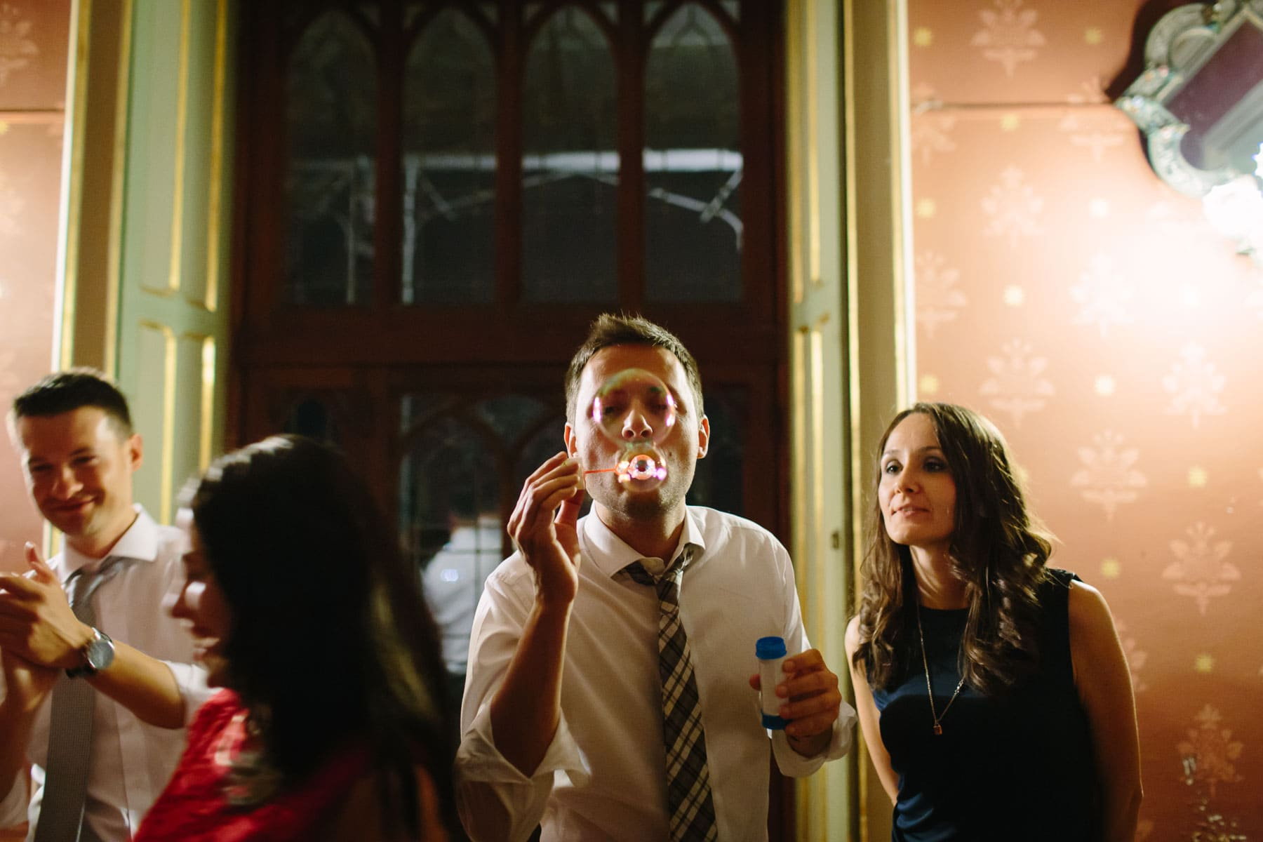 Guest blowing soap bubbles towards camera in this destination wedding in Castello Dal Pozzo, Italy wedding.