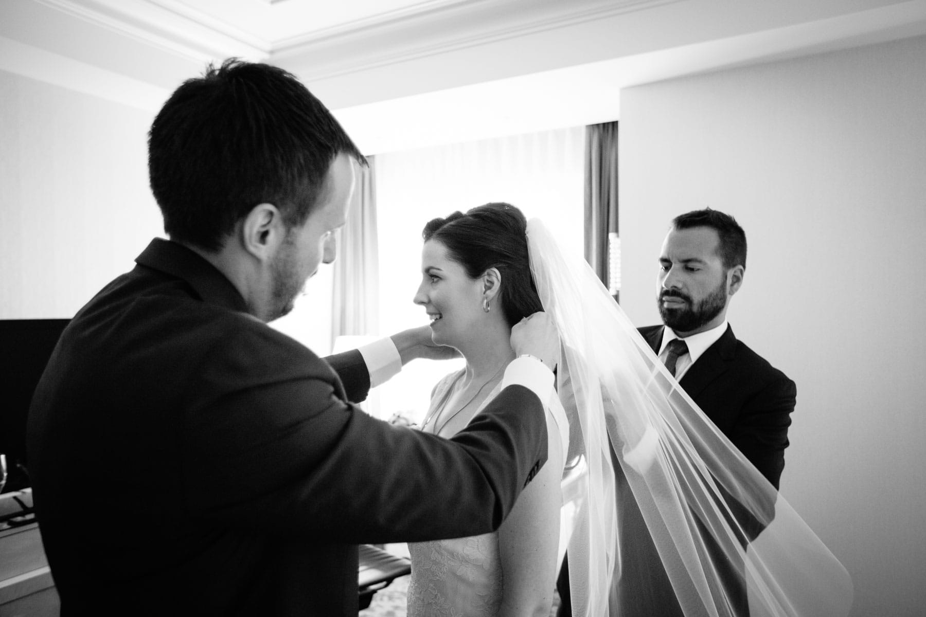 The bride is assisted with putting on her necklace before the marriage ceremony at this Trump Hotel in Toronto