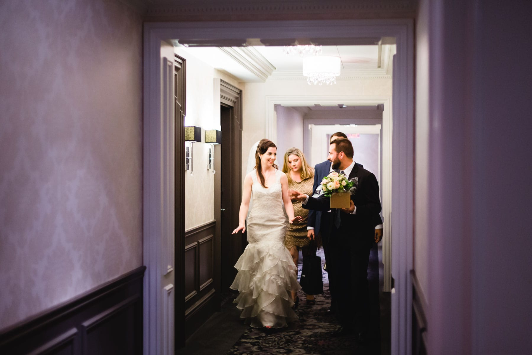 The bride, two men, and one woman walk down the Trump Hotel corridor.