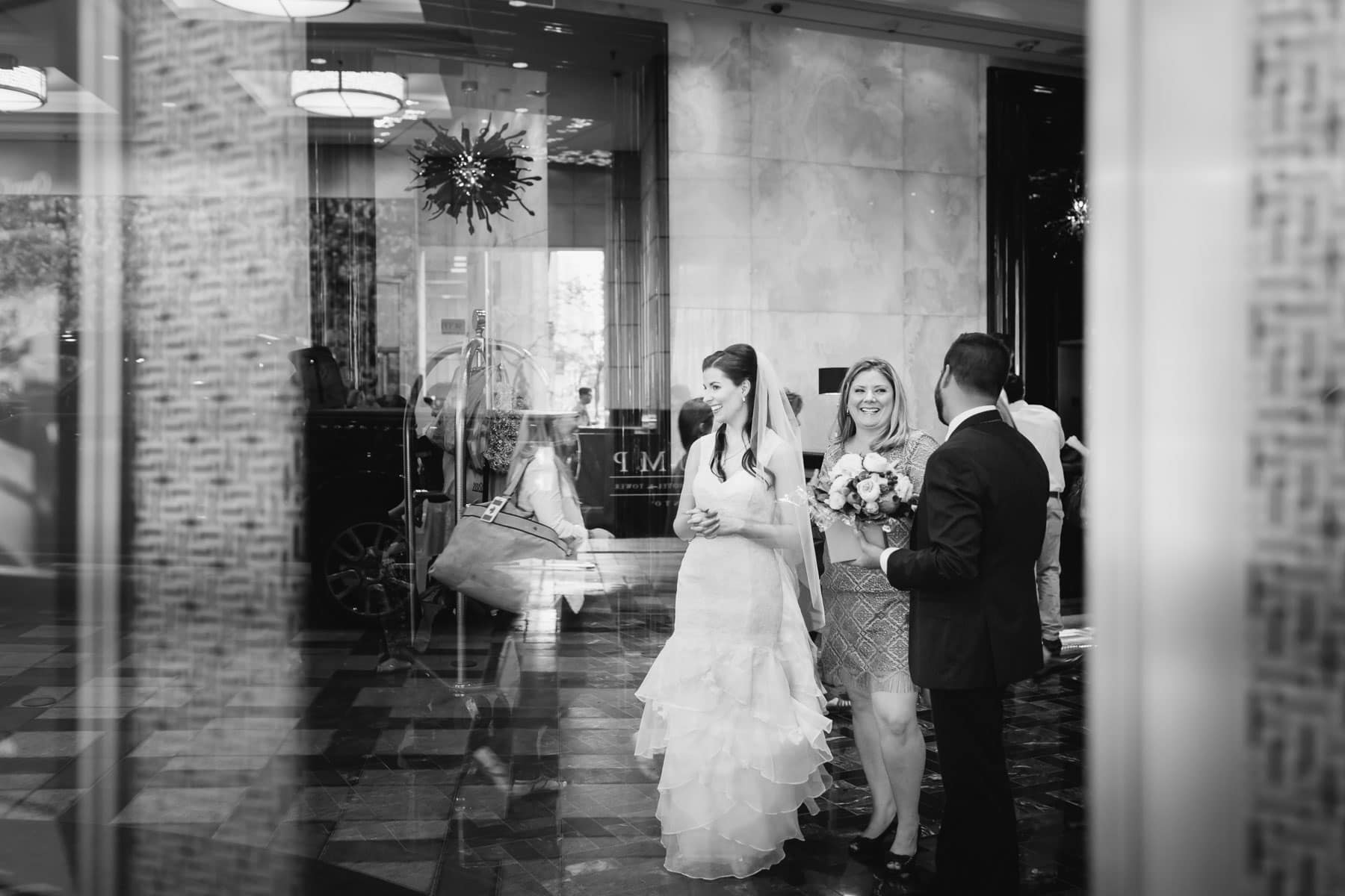 The bride, a man, and the maid of honour stand in the lobby of the Trump Hotel.