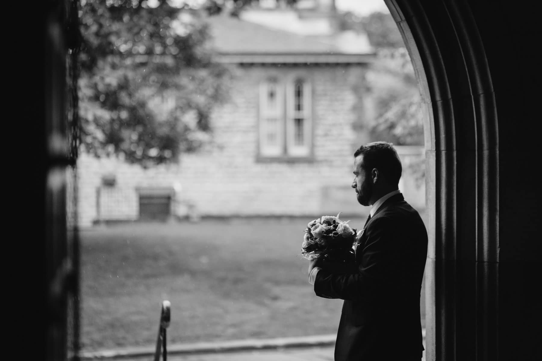 A silhouette of a man standing in the archway of a door waiting for the bride to require help at this Hart House wedding photo.