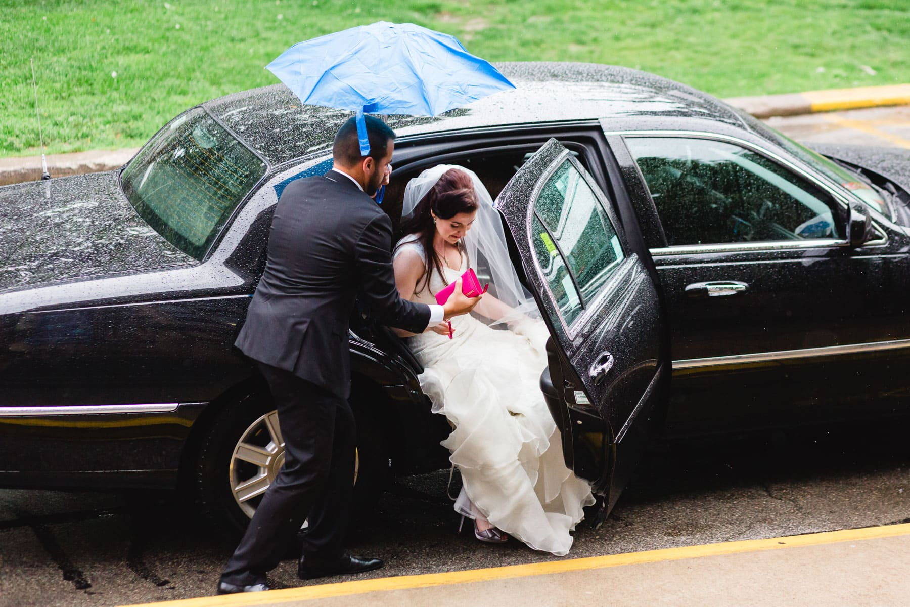 The bride is helped out of the limo by a friend with a tiny umbrella in this Hart House wedding photo.