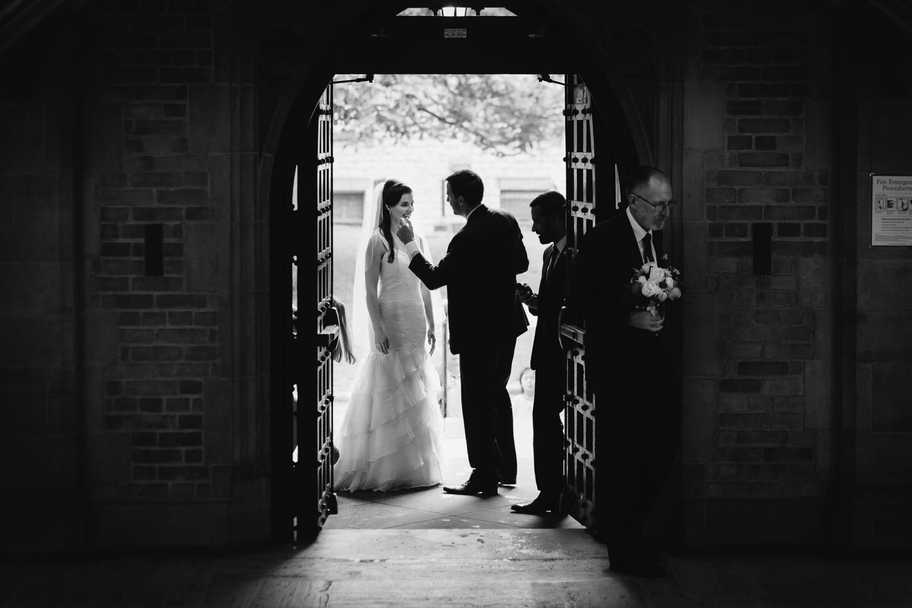 The bride stands in the doorway as her brother adjust her lipster and her father walks into the gloomy shadows with her bouquet in this Hart House wedding photo.
