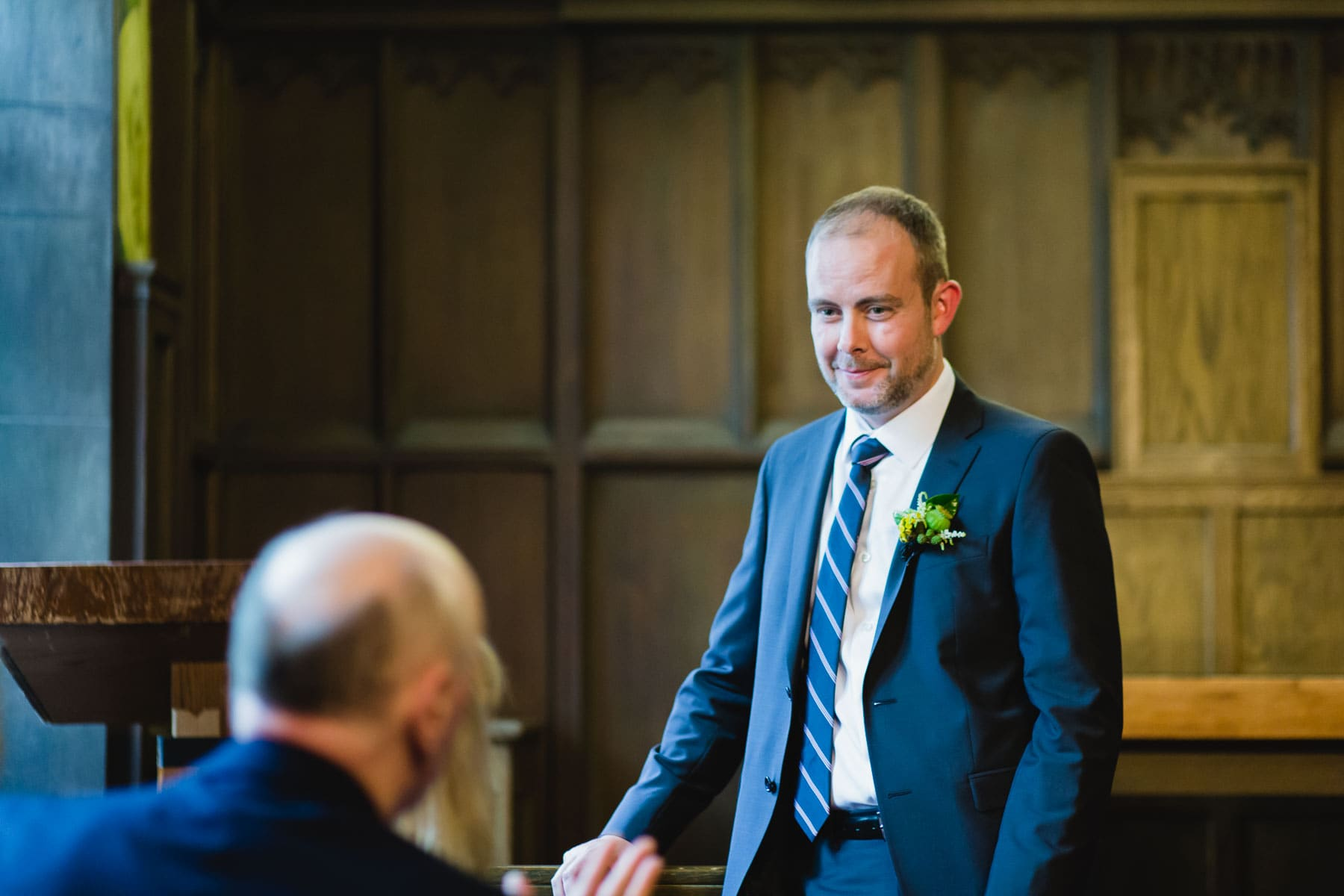 The groom smiles while standing confidently in the ceremony location of Hart House