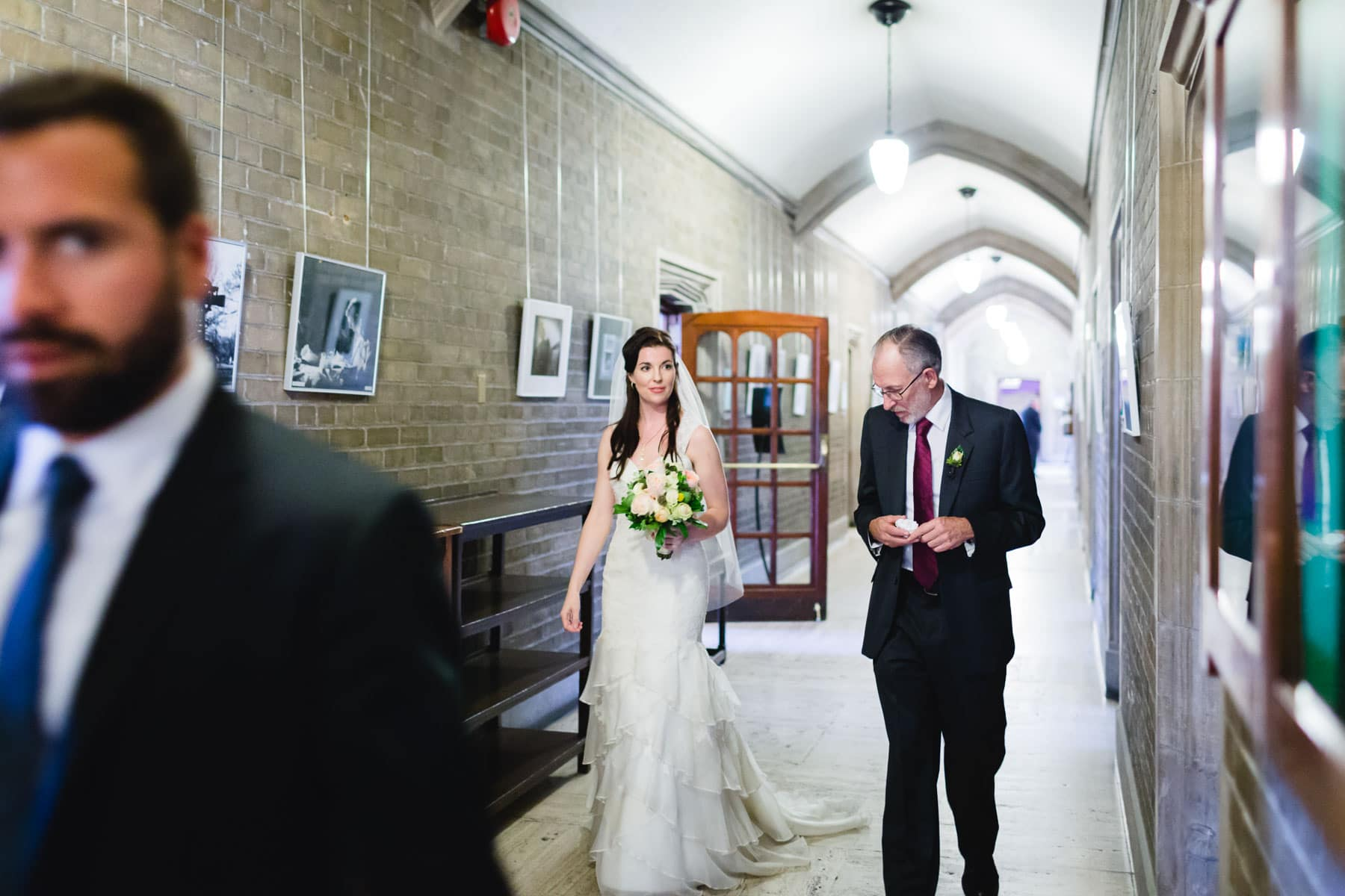 The bride and her father walk through the hallway of Hart House.