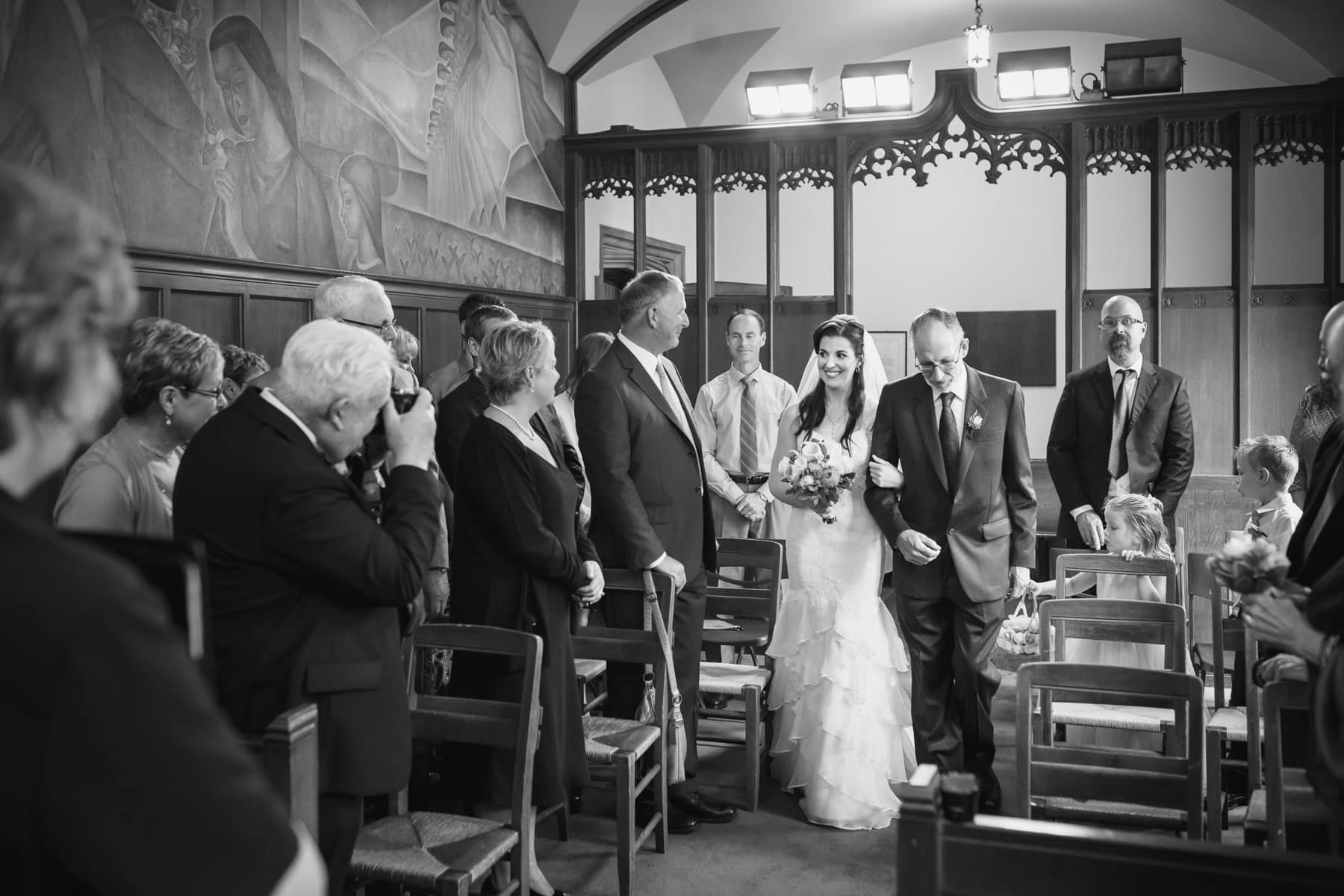 The bride's father walks her down the aisle in this Hart House wedding photo.