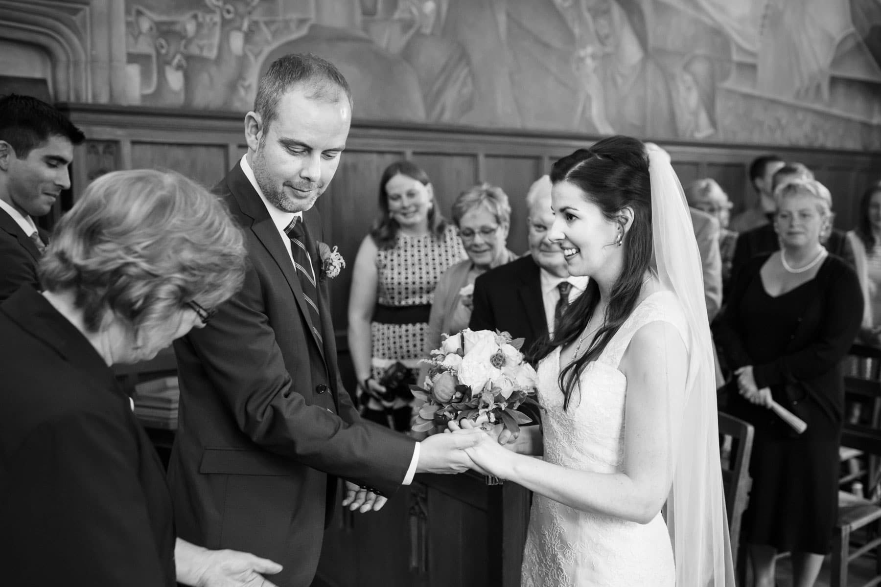 The bride and groom hold hands while smiling at the female wedding officiant and surrounded by guests in this Hart House wedding photo.