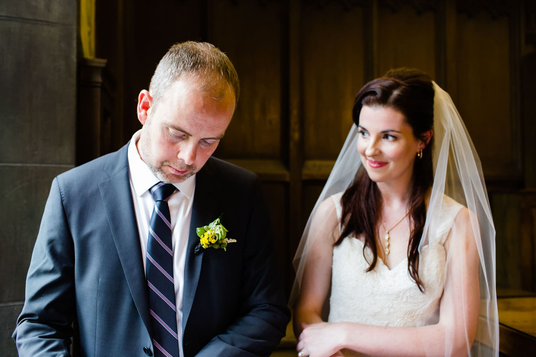The bride watches the groom signing the marriage documents in this Hart House wedding photo.