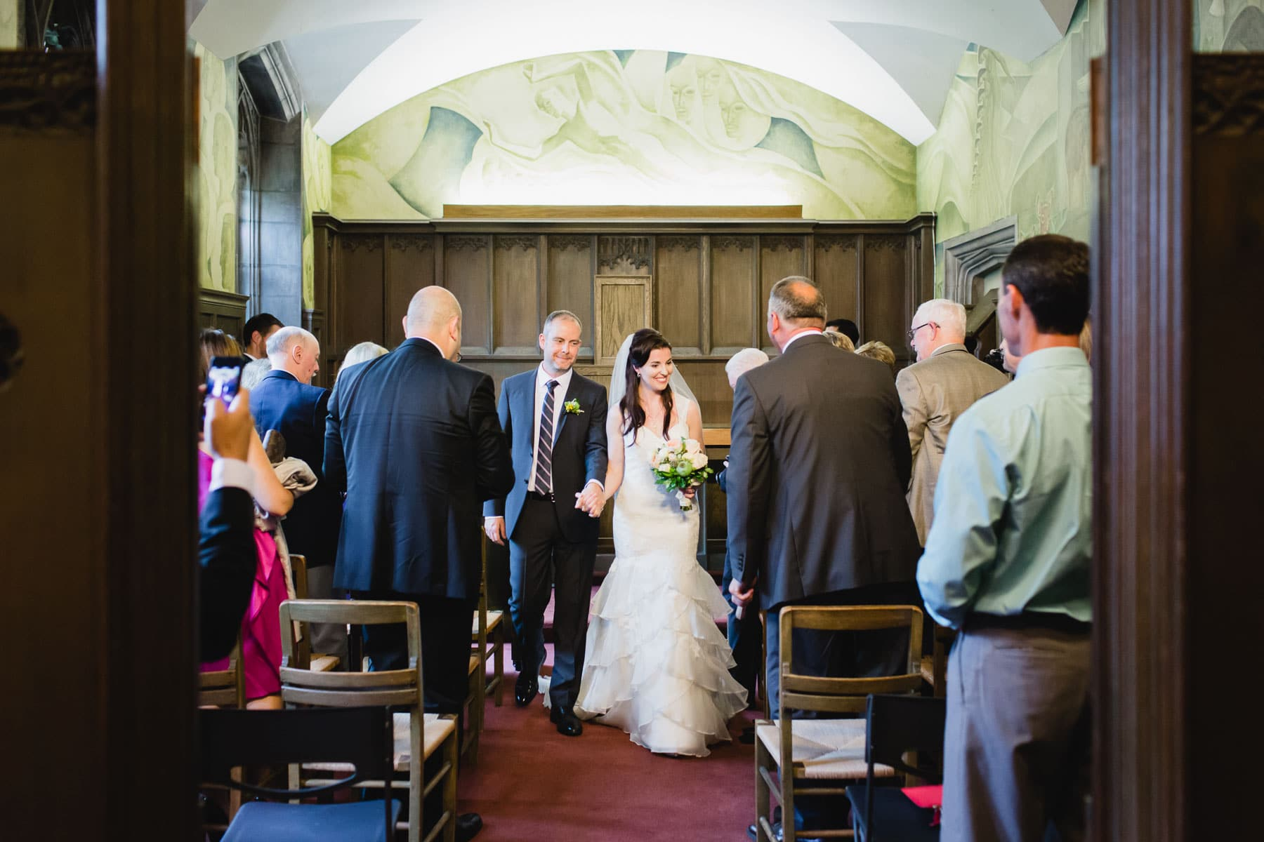 The bride and groom walk down the aisle after the ceremony concluded in this Hart House wedding photo.