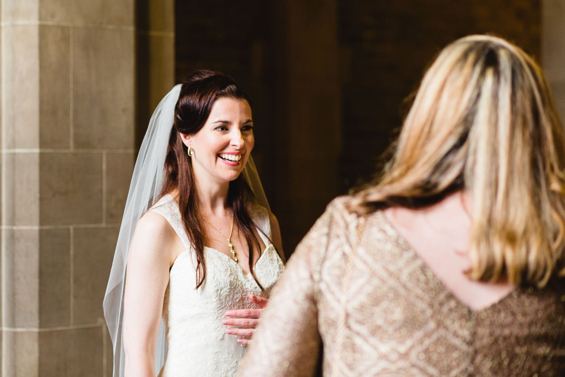 The bride shares a laugh with a friend while standing against a stone wall in this Hart House wedding photo.
