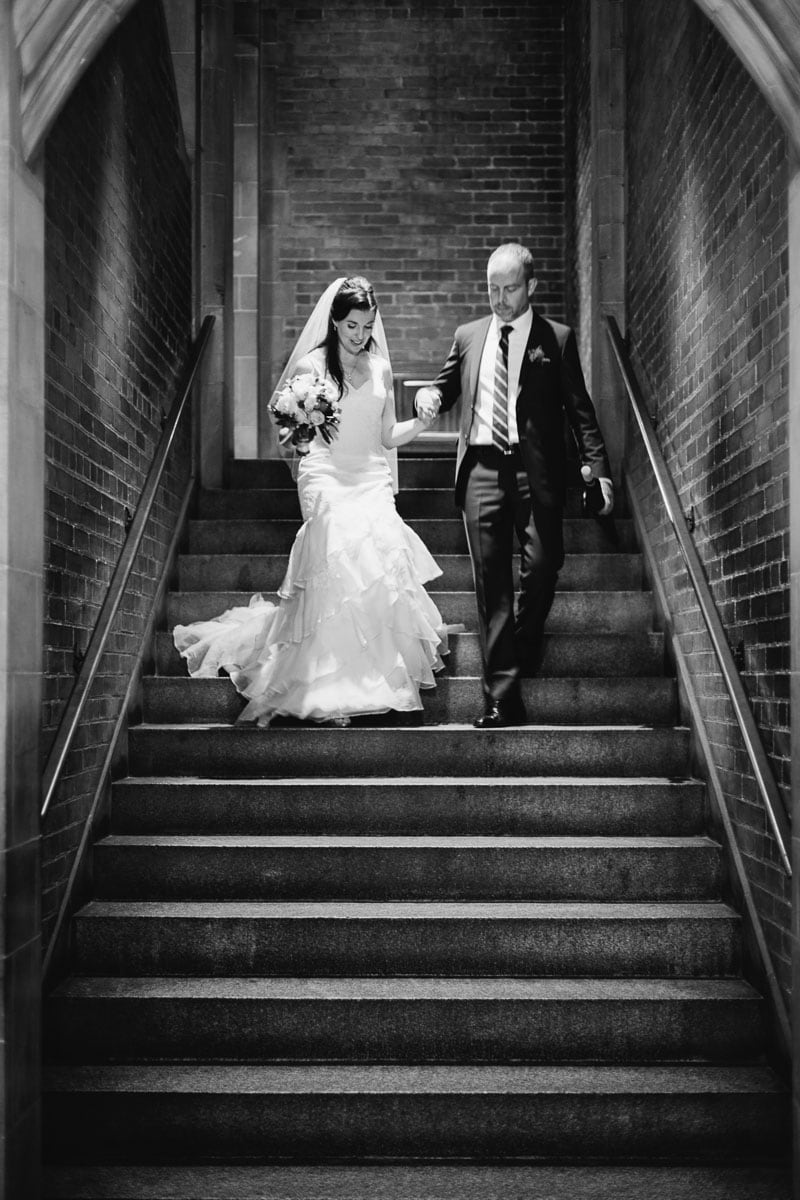 The bride and groom descend the stone stairway at Hart House.