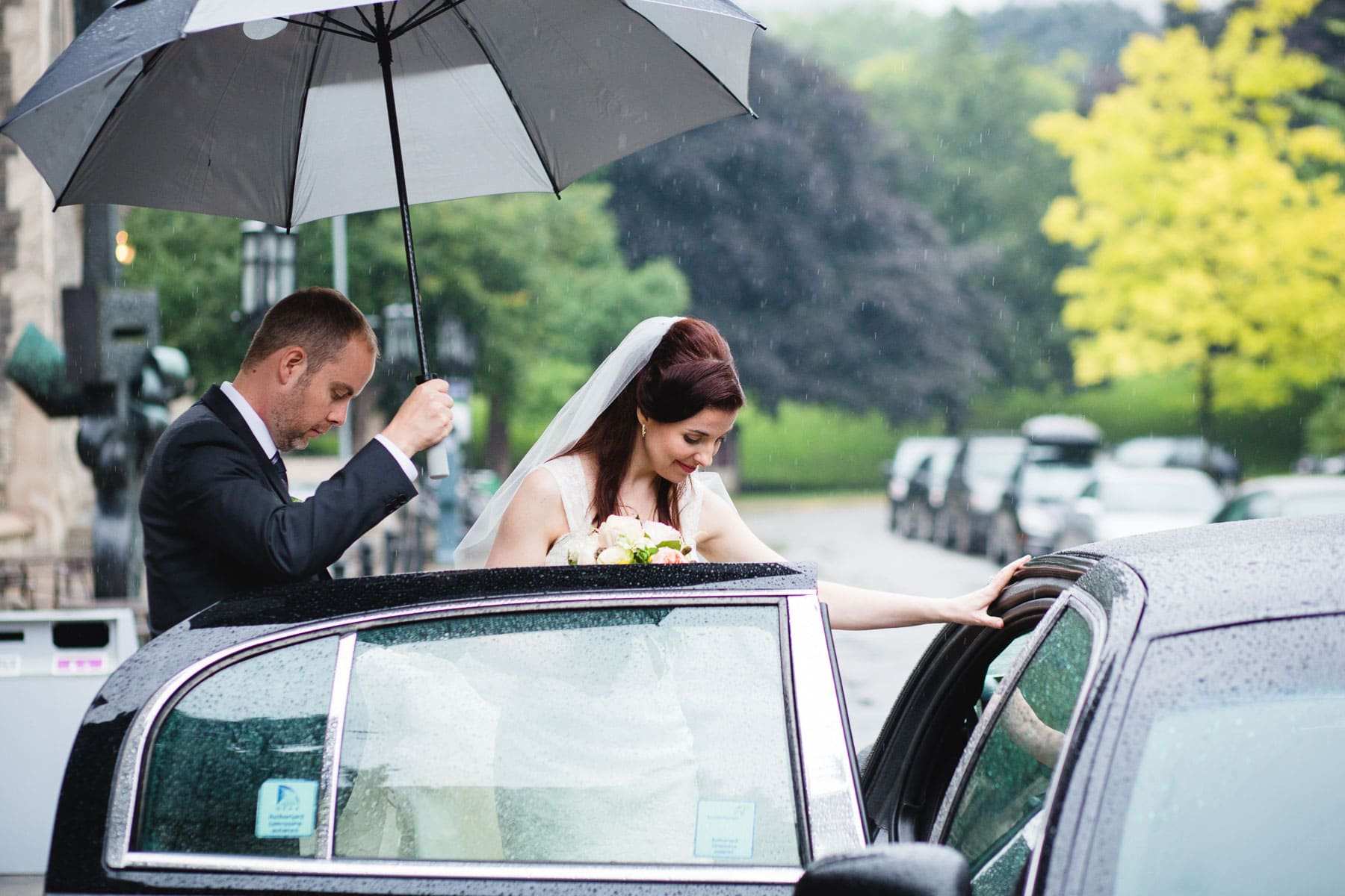 The groom holds an umbrella over the bride as she gets into their limo during a rainy day at this Hart House wedding.