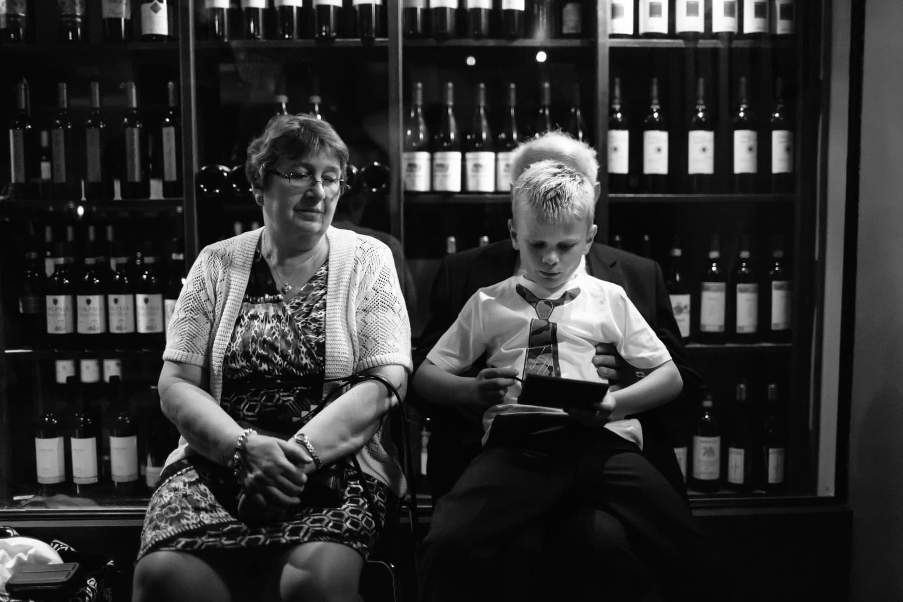 A boy sits on his grandfather's knees, playing video games as his grandmother watches, in the wine cellar of the Splendido Restaurant wedding reception.
