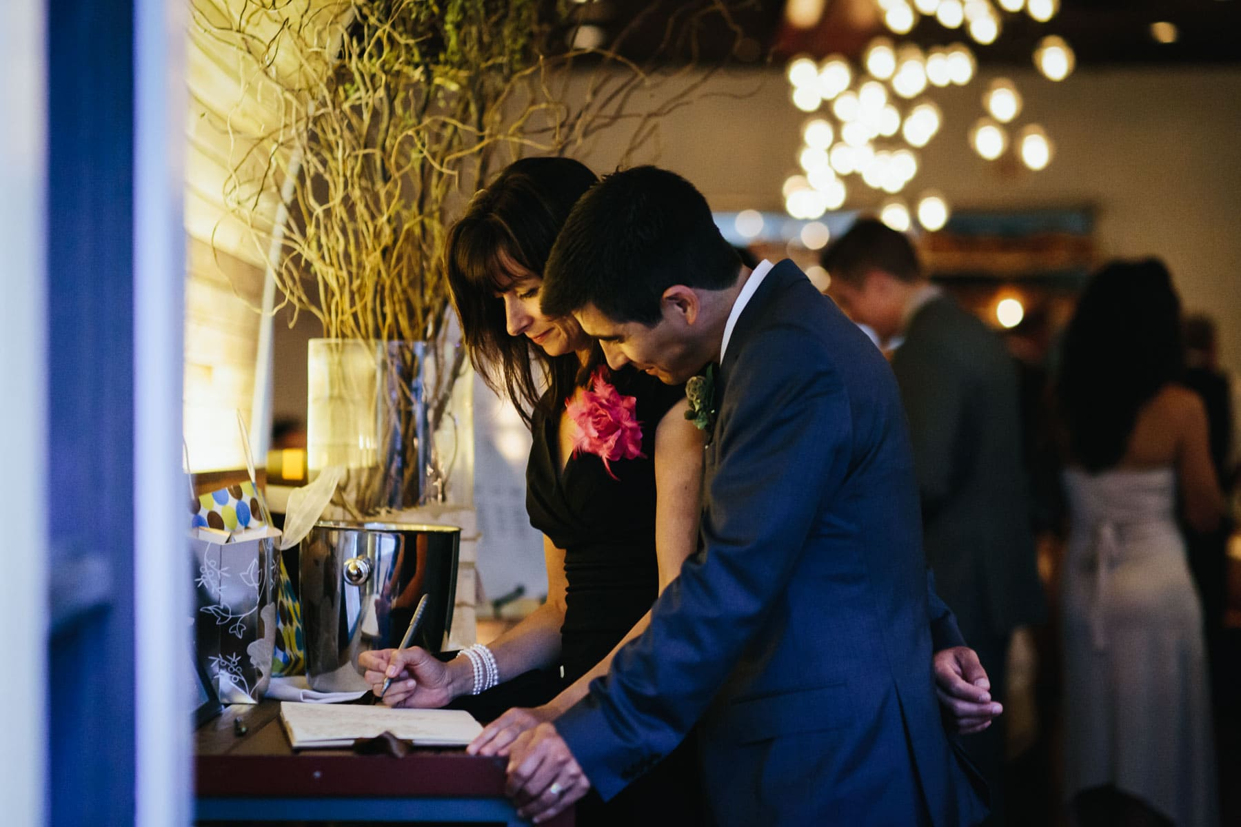 The best man and his wife sign the wedding guest book at the front door at this Splendido Restaurant wedding reception.
