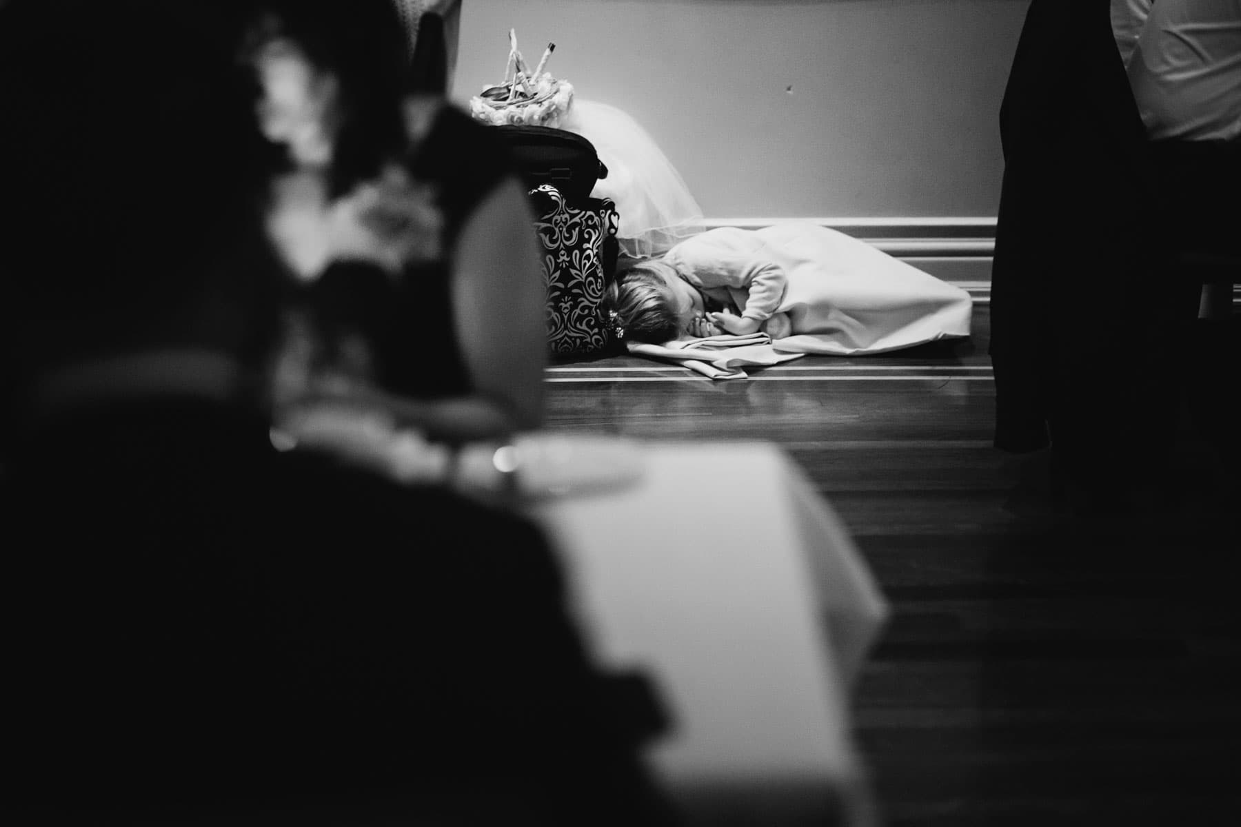 A girl sleeps on the floor covered by a blanket after a fully day at a wedding at this Splendido Restaurant wedding reception.
