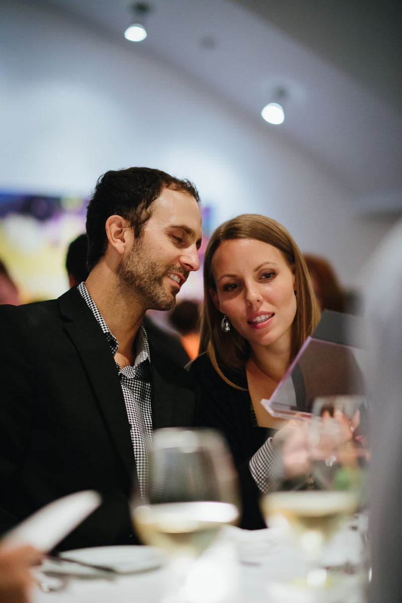 Two guests examine the dinner menu while seated at this Splendido Restaurant wedding reception.