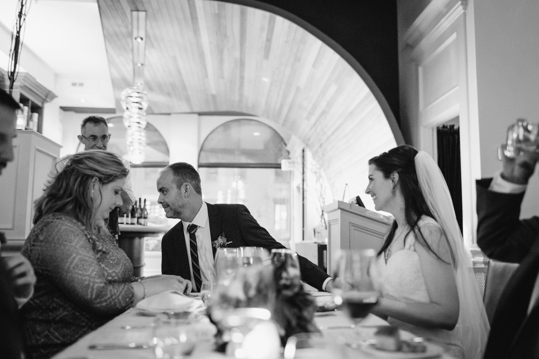 The groom talks to someone off-frame while holding the bride's hand at the dinner table at this Splendido Restaurant wedding reception.
