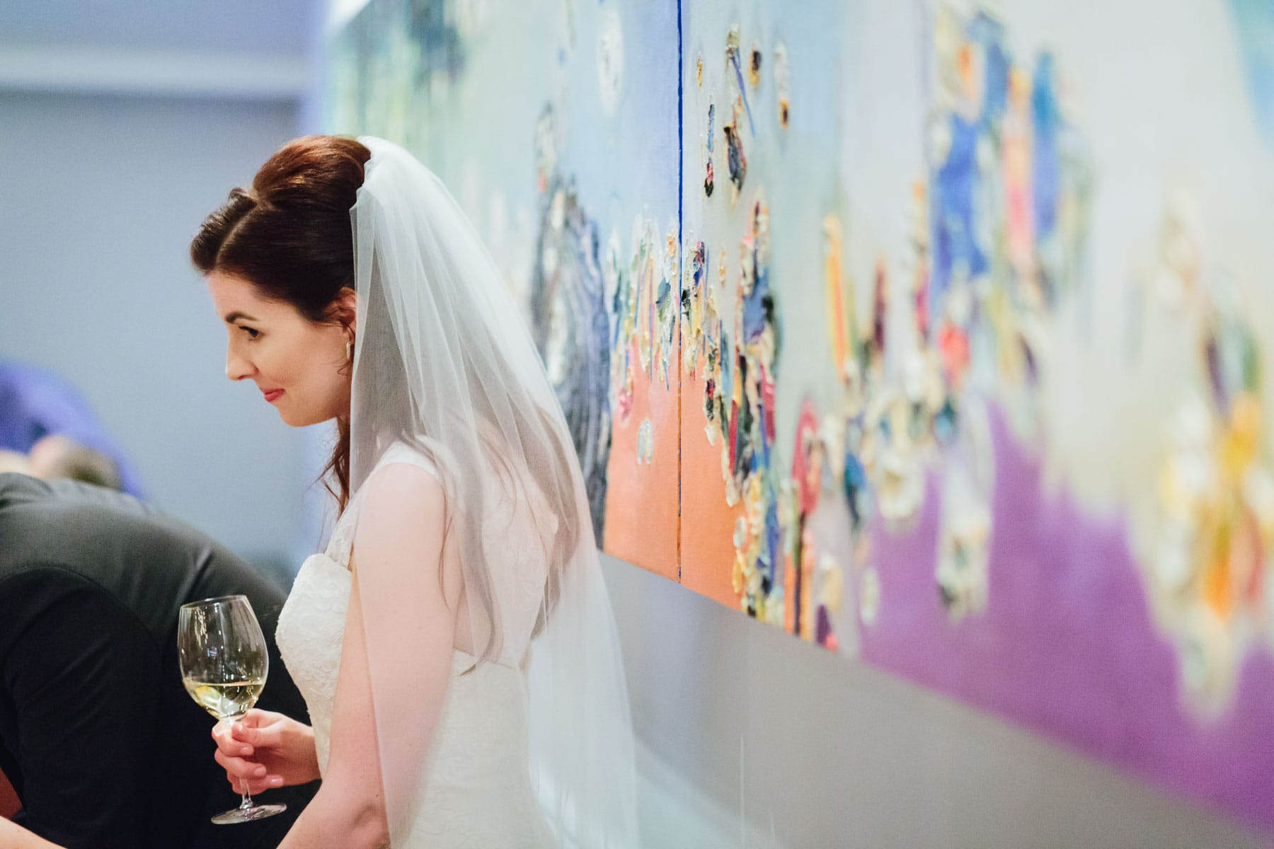 The bride stands next to a large painted canvas in the Splendido Restaurant wedding reception.