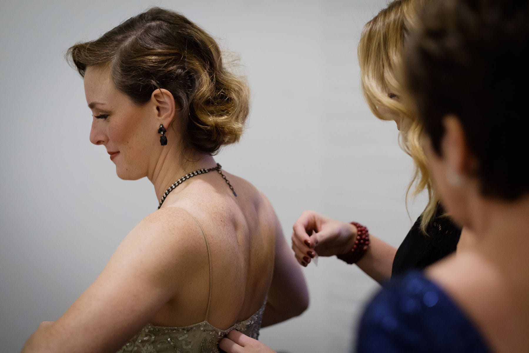 Bride is assisted with her dress by bridesmaids in the bridal suite at The Burroughes building wedding.