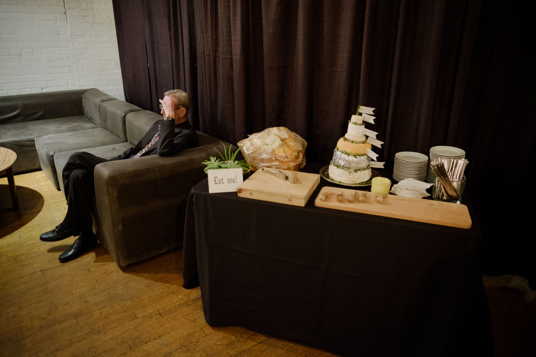 A man sits on a couch with a cake made of cheese on a table in foreground at The Burroughes building wedding.