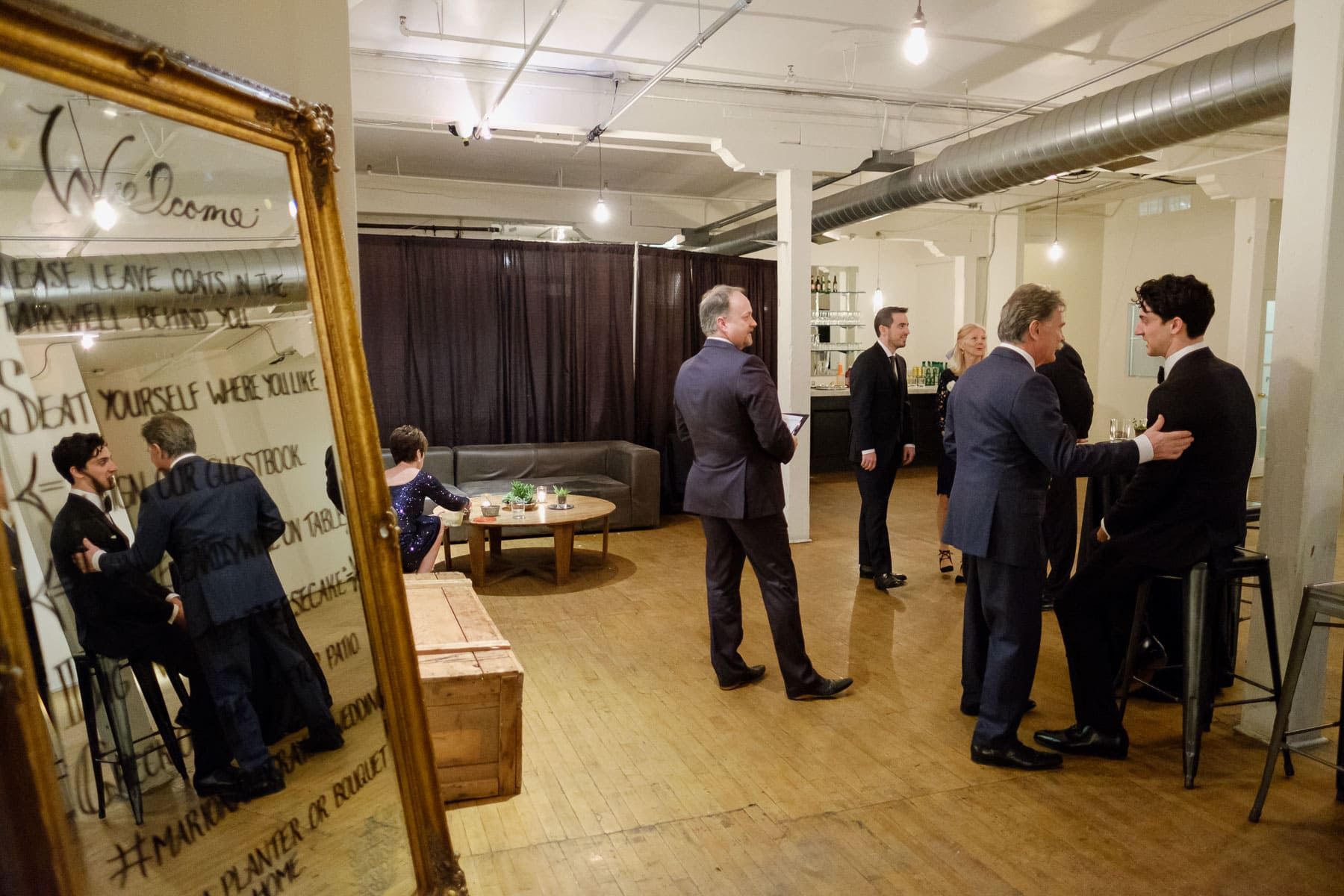 Several people, including the groom, reflected through mirror, just before ceremony at The Burroughes building wedding.