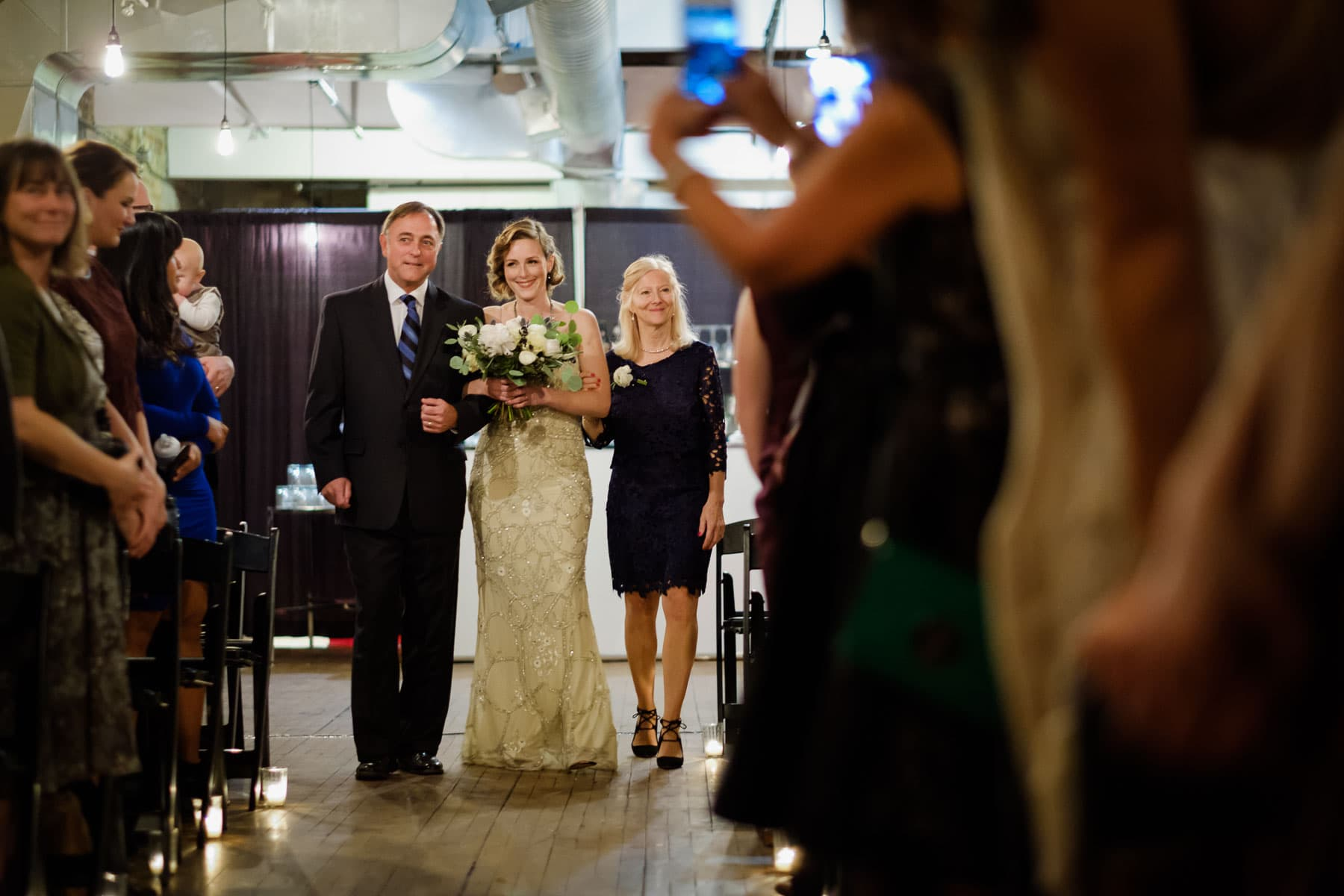 Bride is walked down aisle by both parents at The Burroughes building wedding.