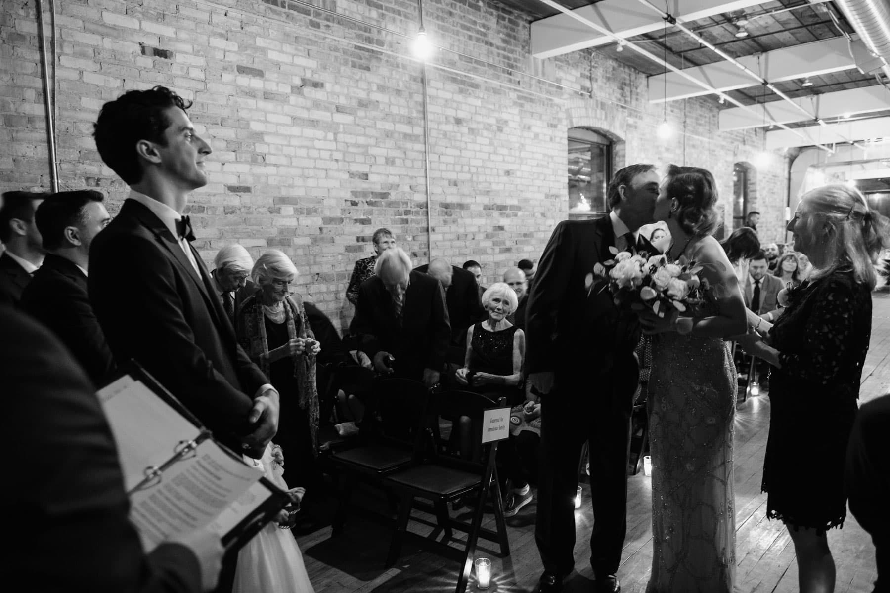 Groom watches as bride kisses father just before the ceremony at The Burroughes building wedding.