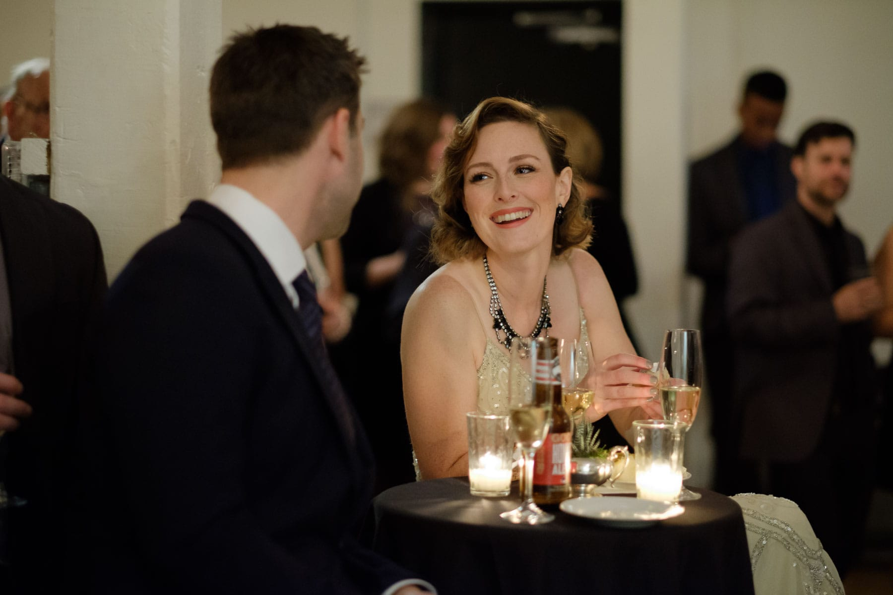 The bride is illuminated by candlelight, laughs to a guest during speech at The Burroughes building wedding.