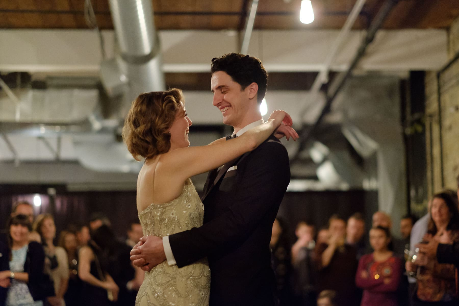 The bride and groom smile at each other during first dance with crowd in background at The Burroughes wedding.