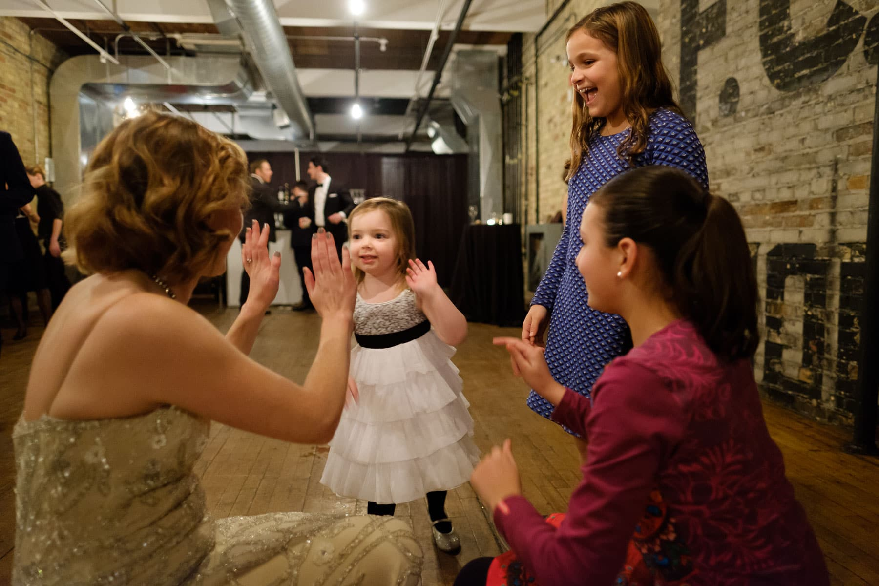 Bride high fives the flower girl on the dancefloor of the The Burroughes building wedding.