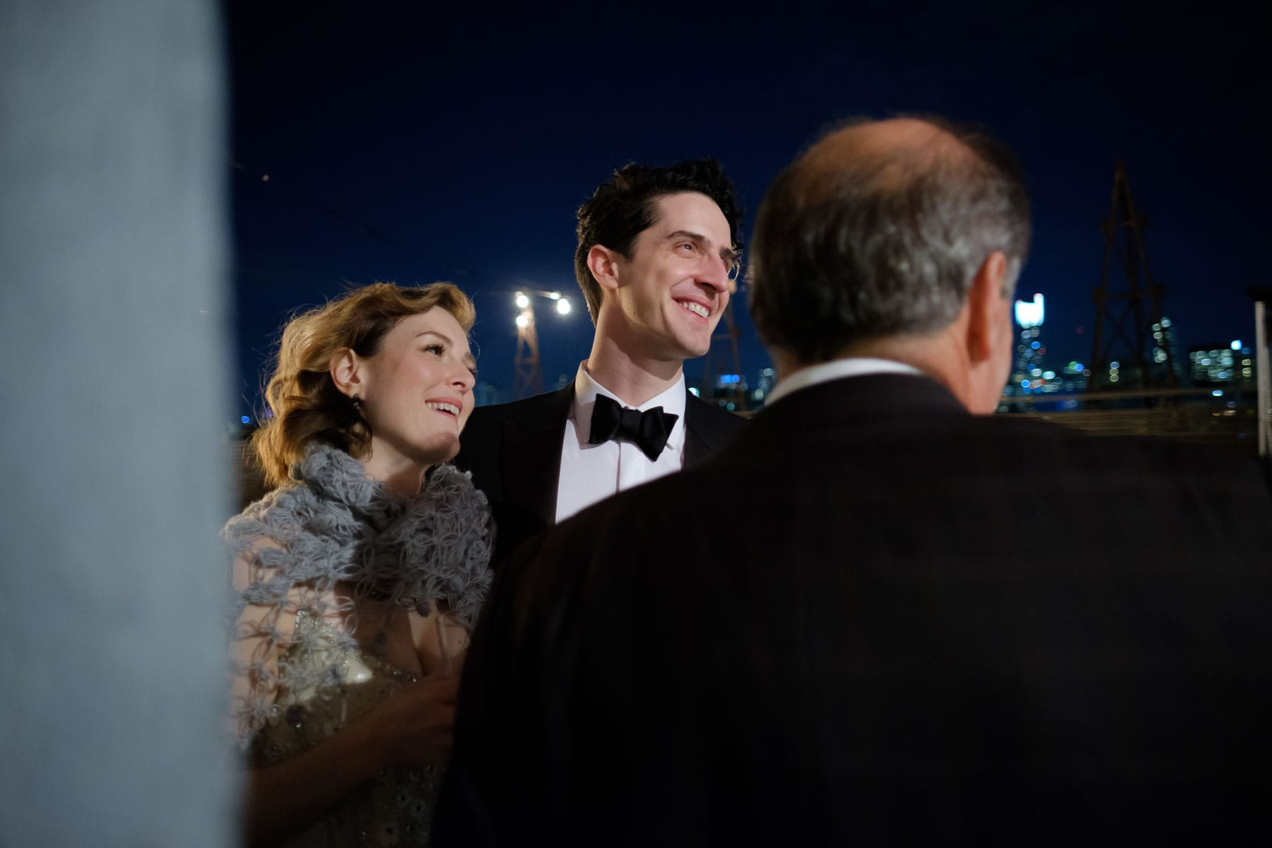 Bride and groom smile and chat with guest on rooftop at night at The Burroughes building wedding.