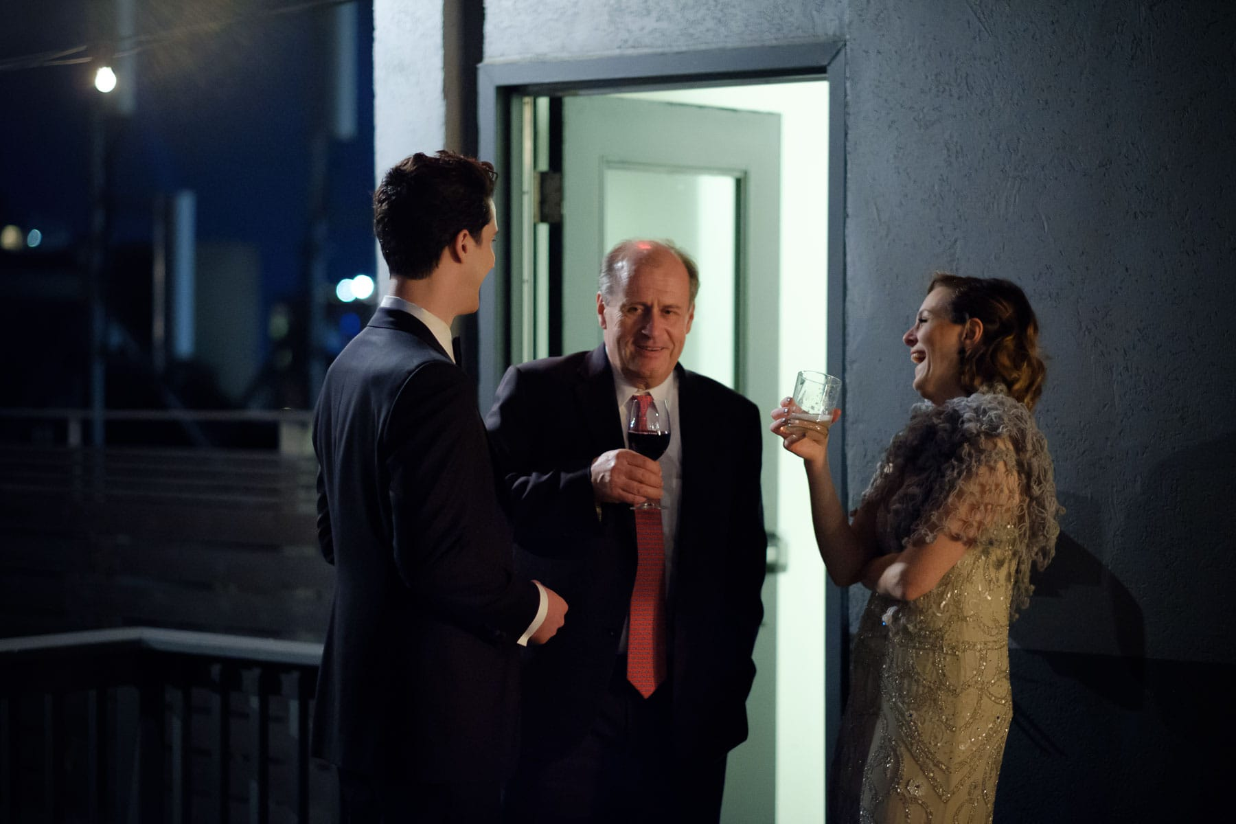Bride and groom chat with a guest on the rooftop at The Burroughes building wedding.