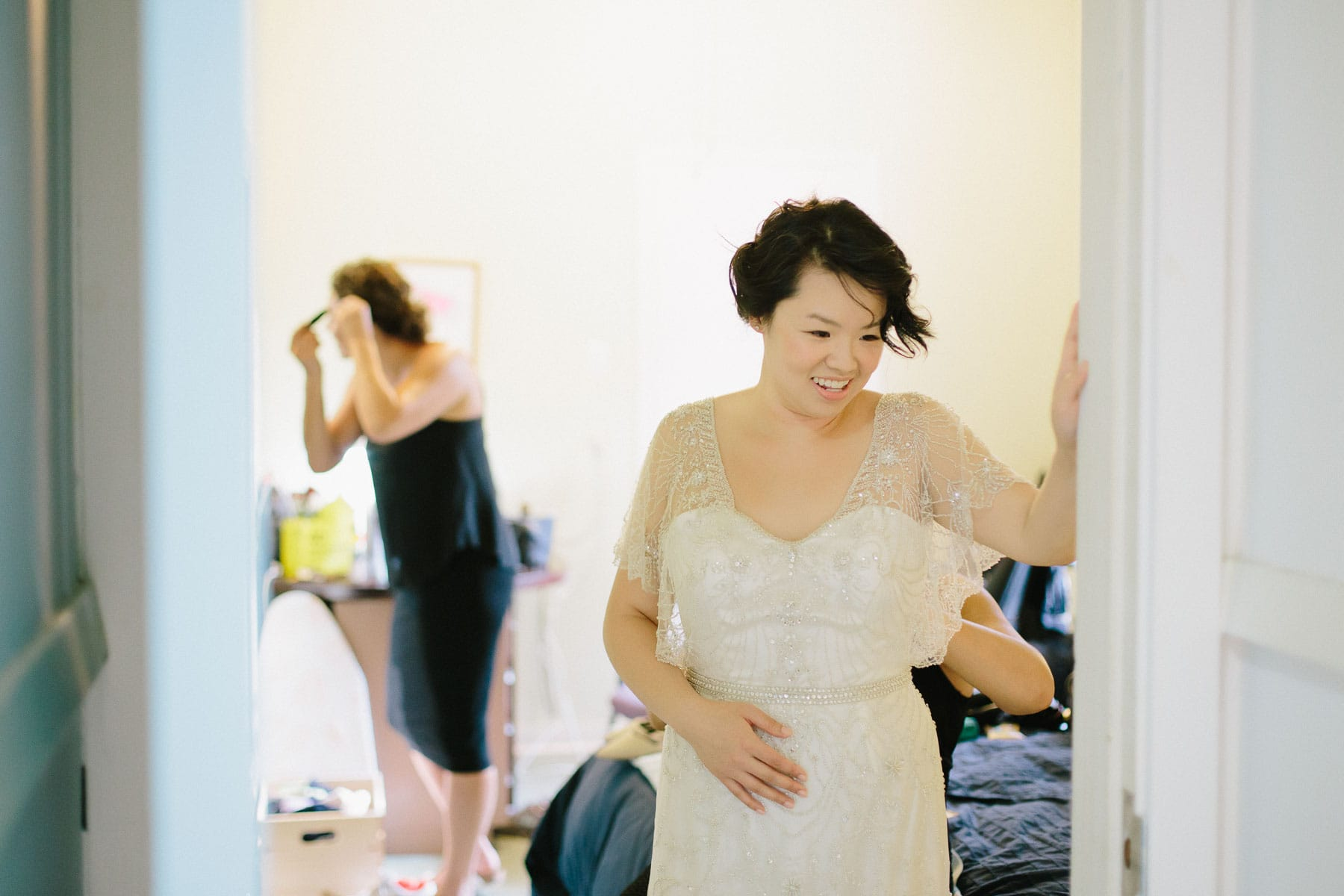 Bride puts on dress in room, Artscape, Toronto Island wedding