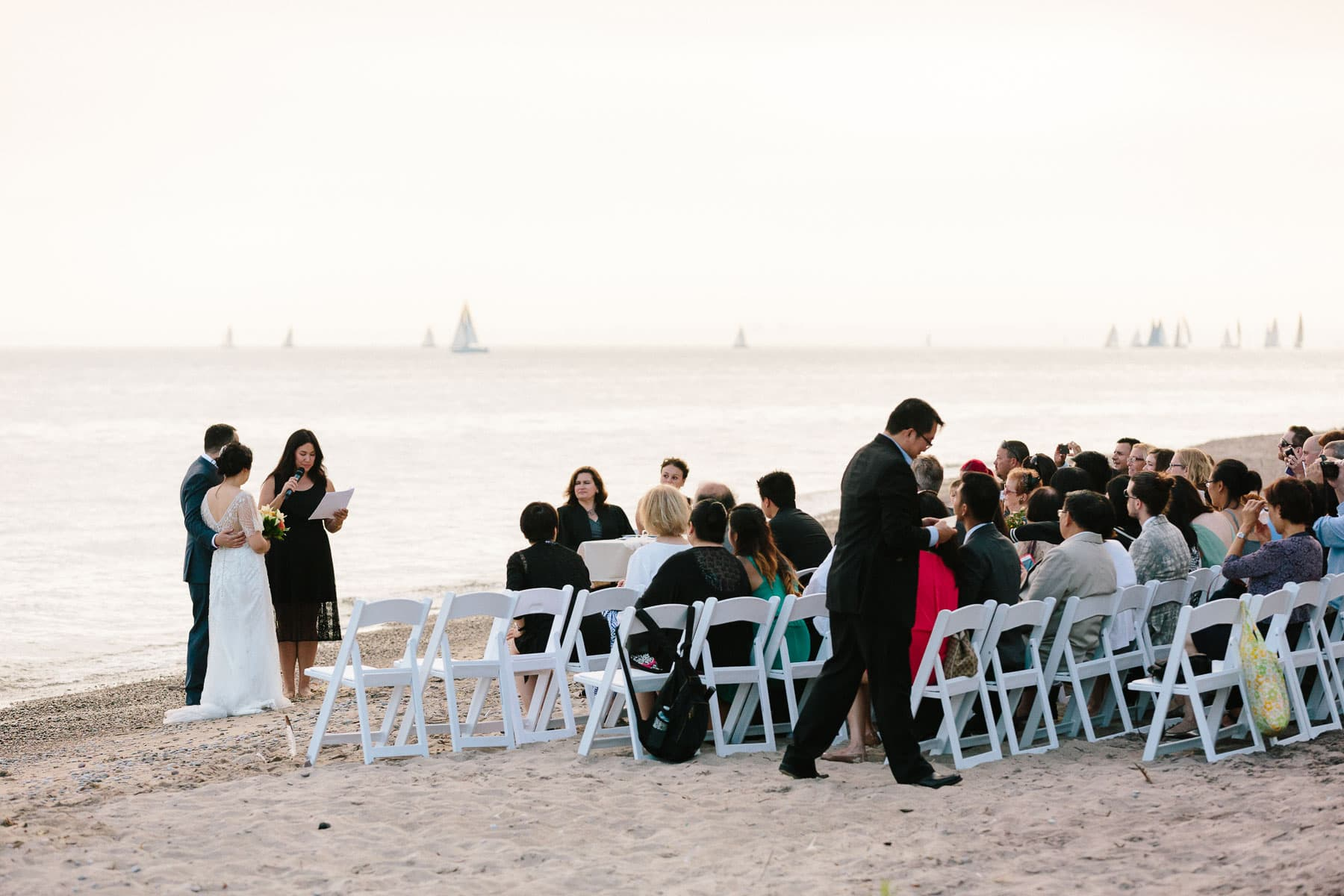 Groom and Bride during beach ceremony, sail boats, Artscape, Toronto Island wedding