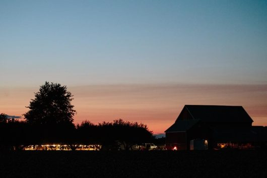 distant barn and tent during twilight - barn wedding photography