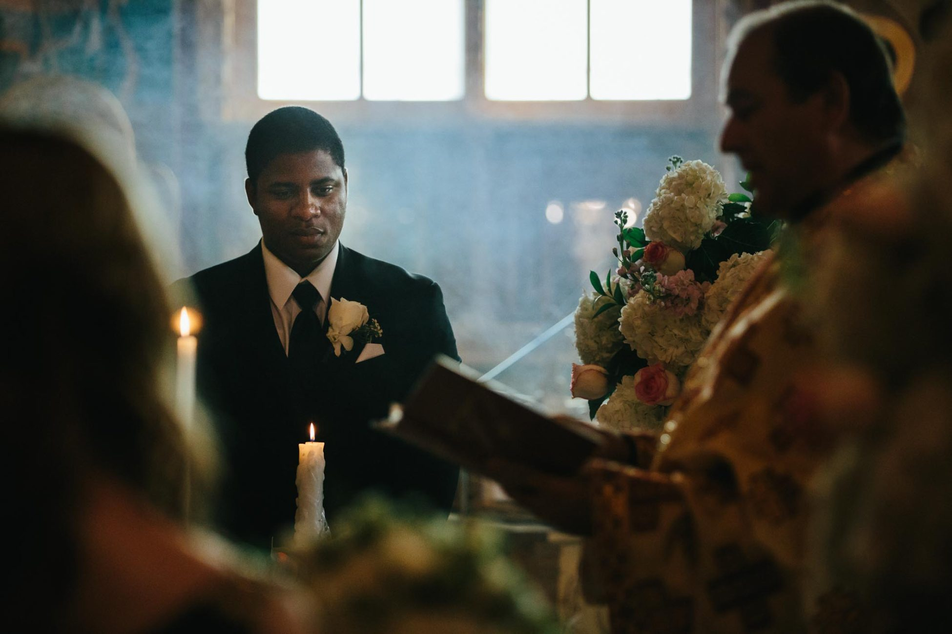 Cinematic wedding photography of the best man standing in hazy light during orthodox ceremony at Saint George Romanian Orthodox Church