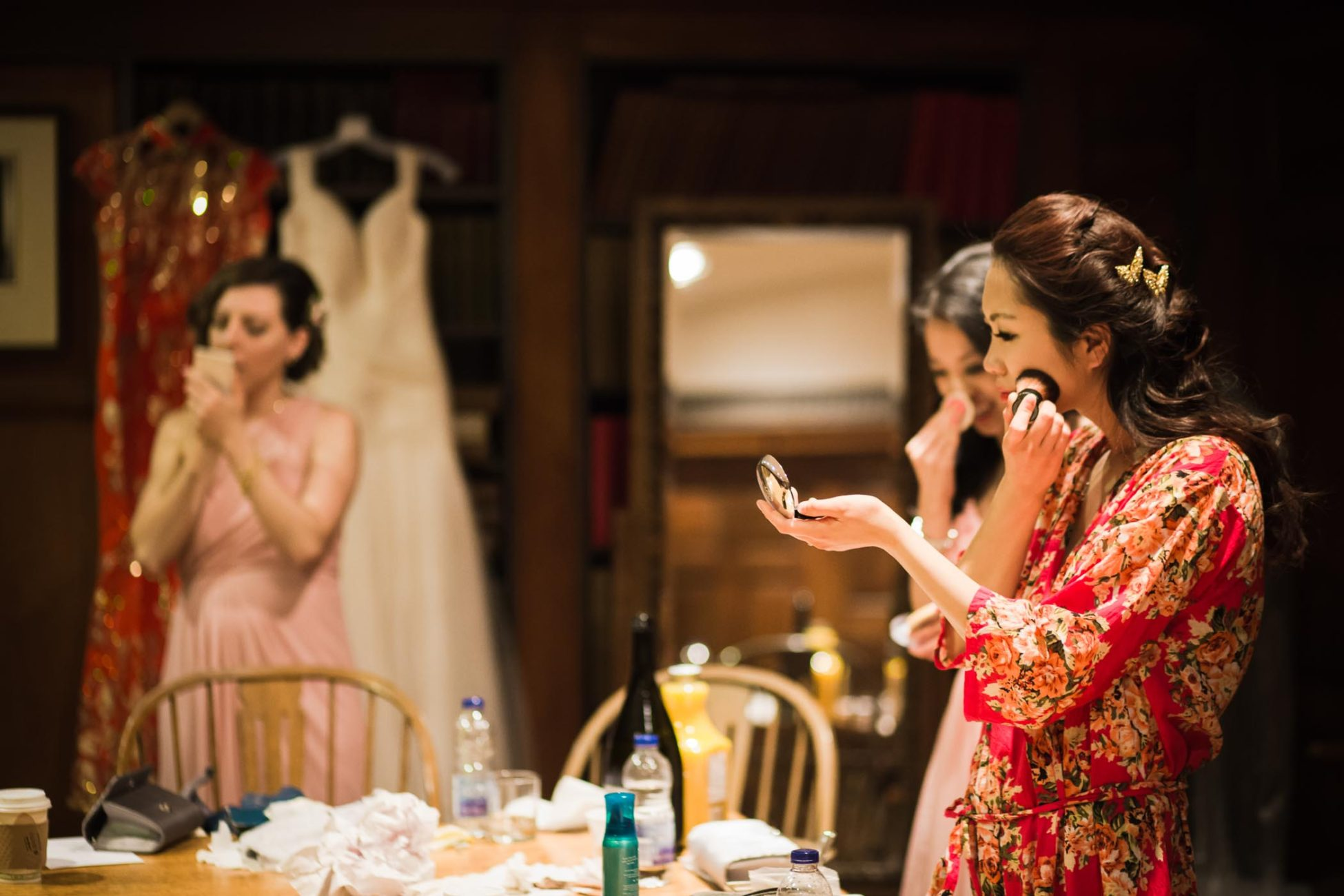 The bride dressed in a red robe doing makeup with bridesmaids before dinner in this Hart House wedding photography by Pavel Kounine.