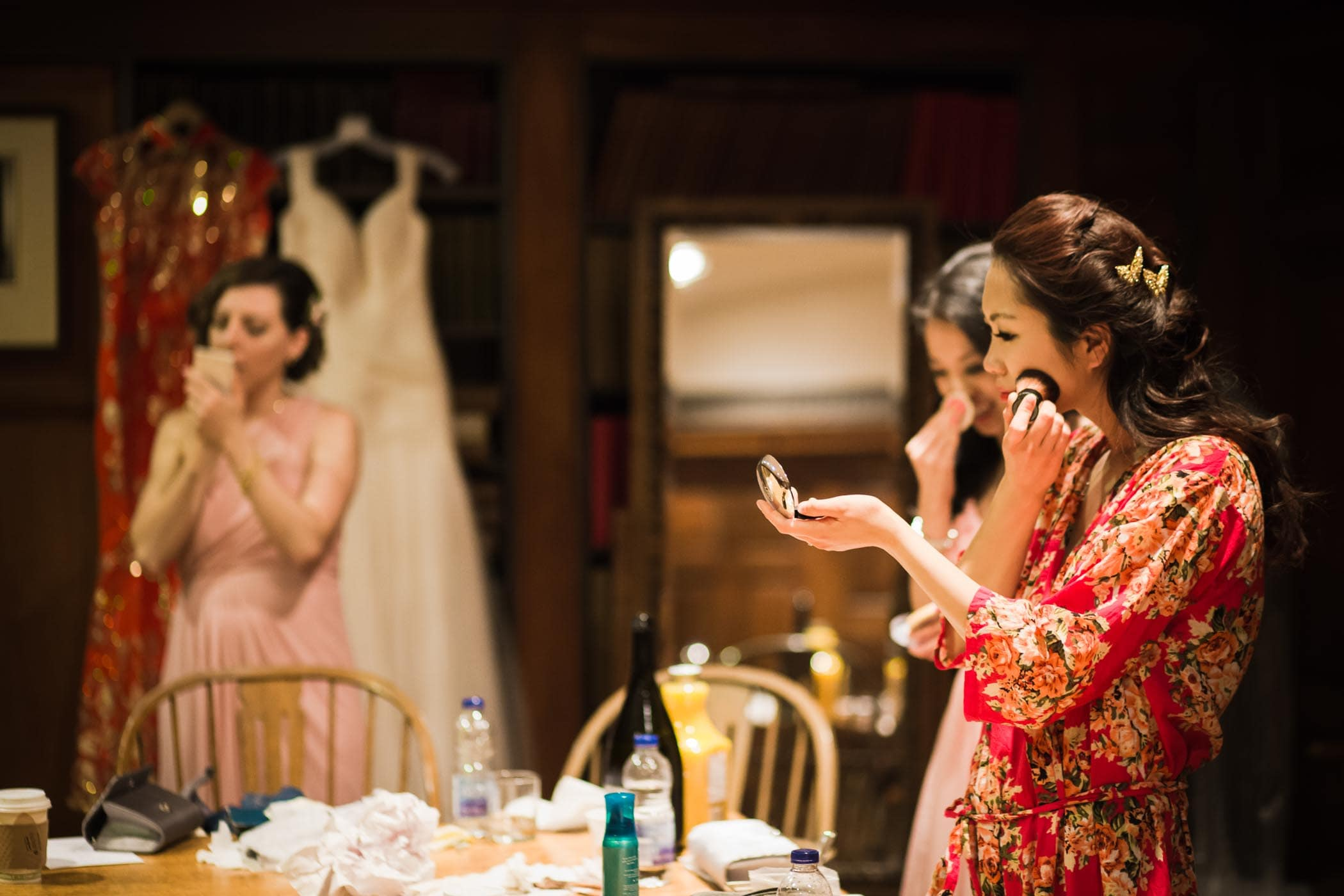 The bride dressed in a red robe doing makeup with bridesmaids before dinner in this Hart House wedding.