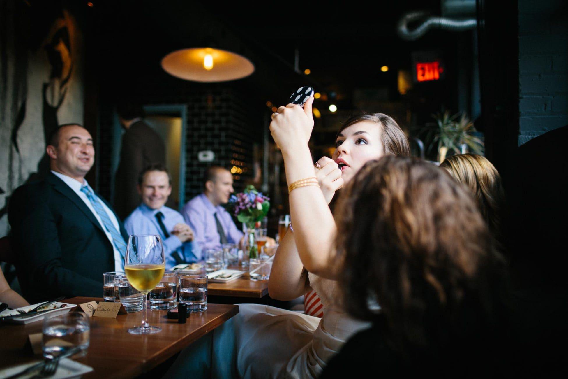The bride applying her lipstick in small vanity mirror in restaurant wedding reception. Documentary wedding photography by Pavel Kounine.