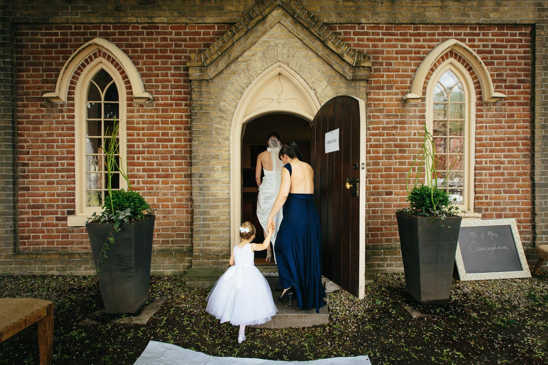 The bride, bridesmaid, and flower girl enter Enoch Turner Schoolhouse for the wedding ceremony. By Toronto wedding photographer Pavel Kounine.