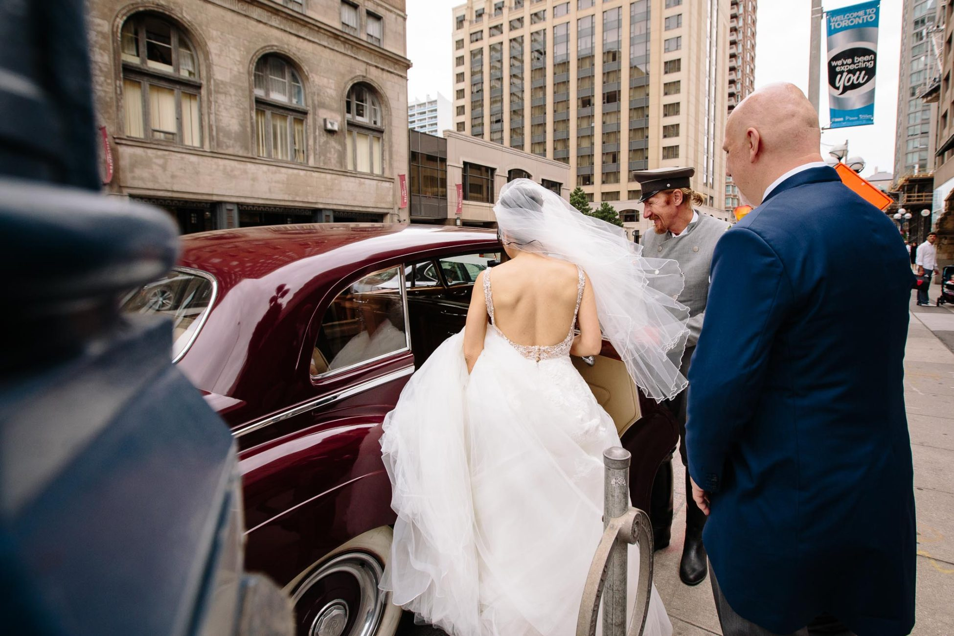 The bride entering a red Rolls Royce limo after wedding ceremony at Church of the Redeemer in Toronto.