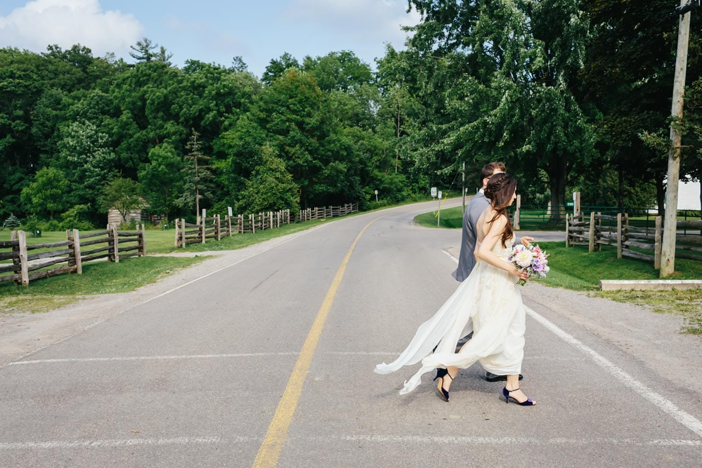 The bride and groom crossing a paved country road from the chapel to the barn at Ball's Falls Conservation Area.